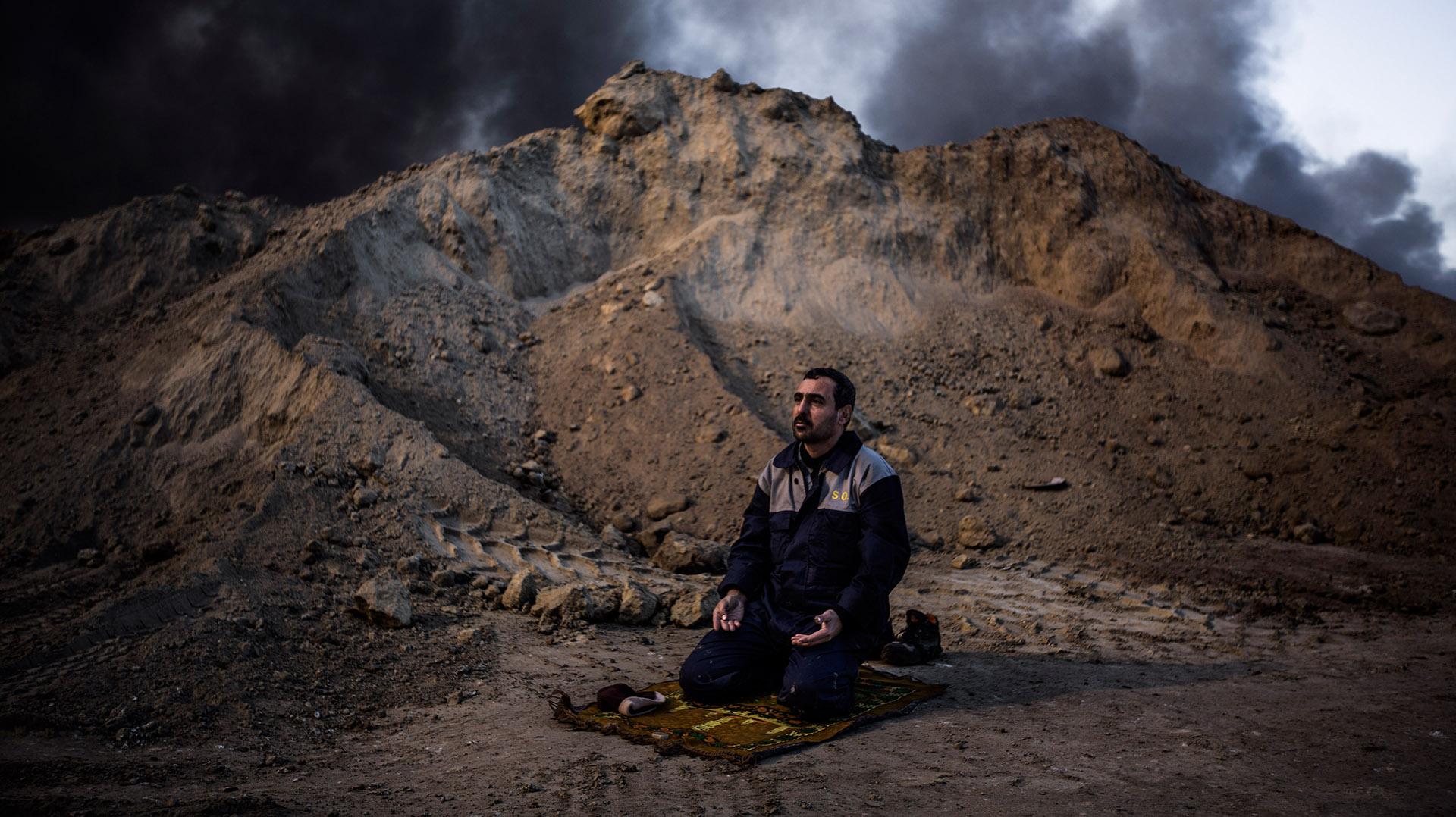 """Mohamed, miembro del cuerpo de bomberos iraquí, reza frente al ardiente pozo de """"El Hoyo"""" antes de enfundarse el traje de protección y comenzar su turno para intentar apagarlo (Pablo Cobos)"""
