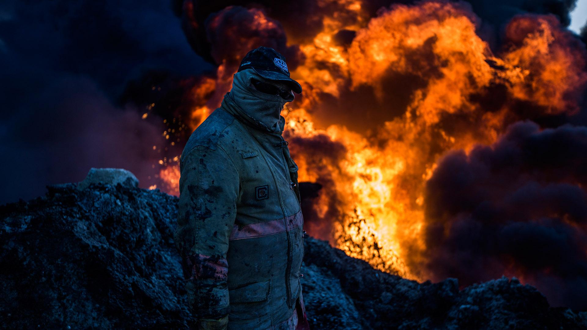 Abdul, ataviado con el equipo de protección, revisa el estado del pozo antes de subir al taladro para comenzar a taponar el pozo de petróleo incendiado. (Pablo Cobos)