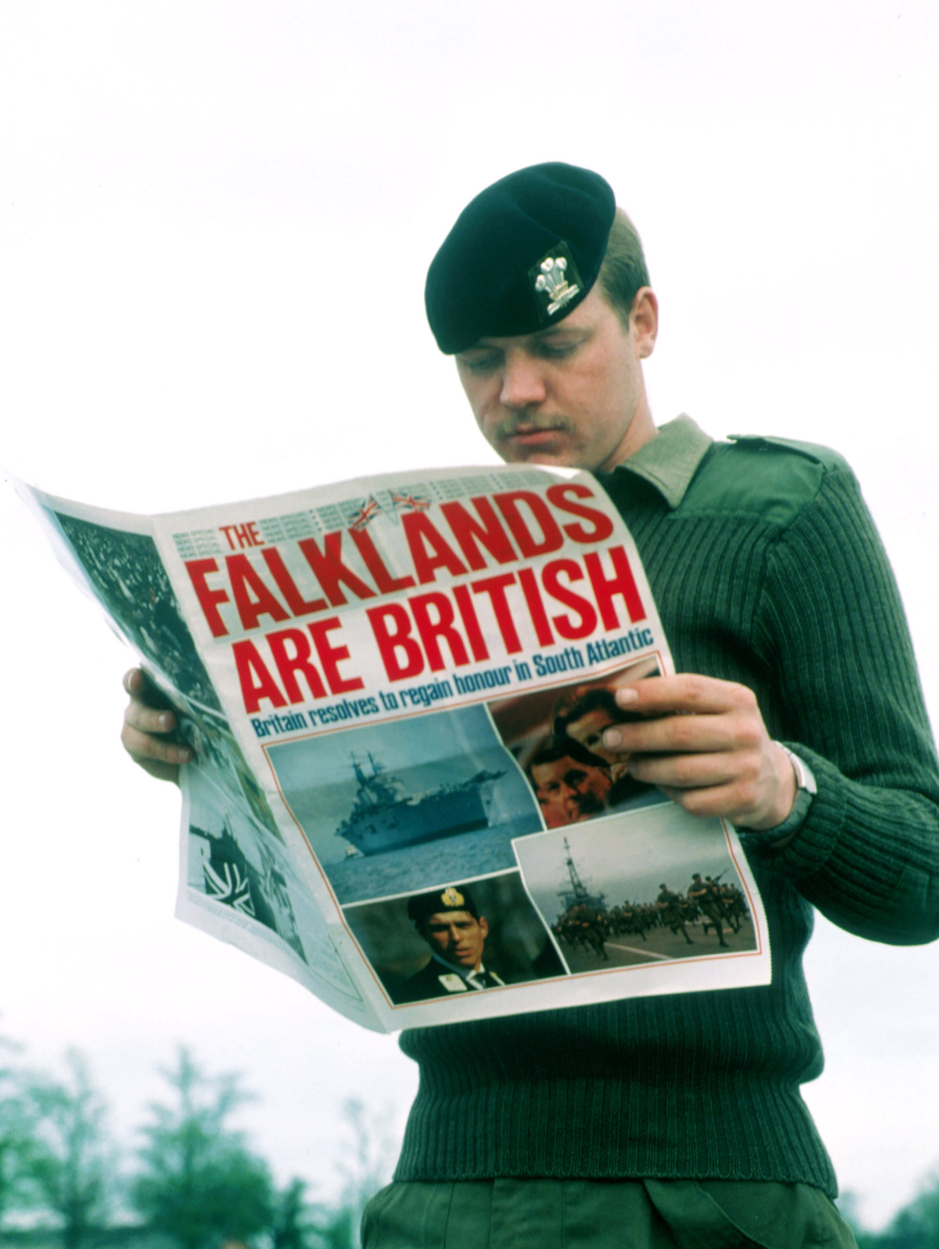 """Un soldado británico lee el diario luego de la recuperación argentina delas Islas Malvinas: """"Las Falklandsson británicas. Gran Bretaña resuelve recuperar el honor en el Atlántico Sur"""", dice el titular en letra catástrofe (Liaison)"""