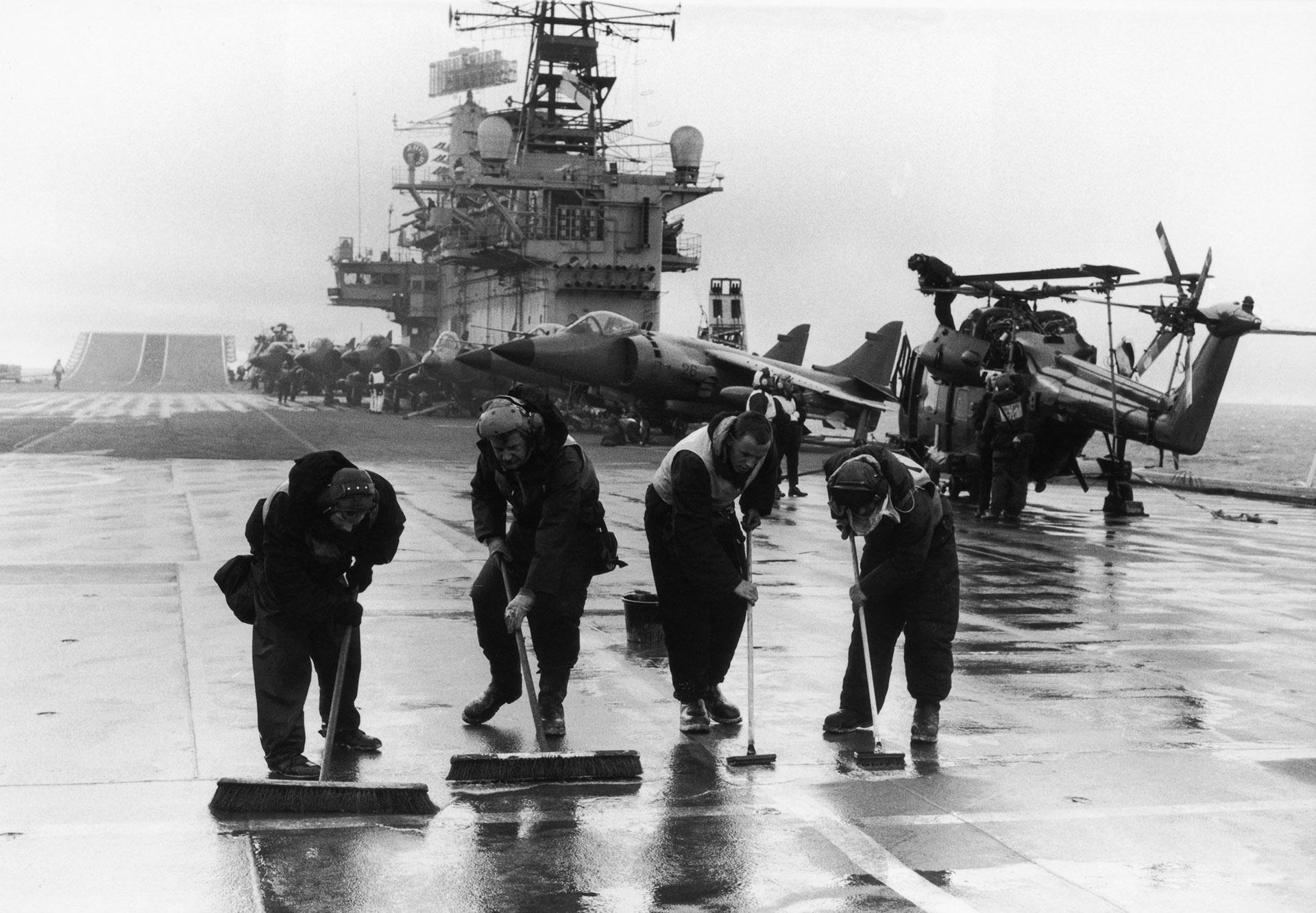 Cuatro hombres limpian la cubierta del portaviones británico HMS Hermes. Llevaba 16 caza navales Sea Harrier, 10 Harrier y 10 helicópteros pesados Sea King, así como un escuadrón de Servicio Aéreo Especial (SAS) y uno de Royal Marines, mayo de 1982 (Martin Cleaver/Pool/Getty Images)