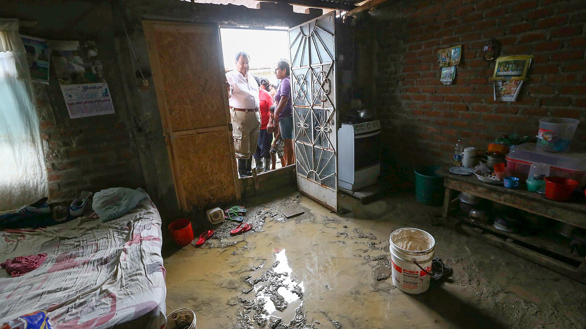 El ministro de Defensa de Perú, Jorge Nieto, observa el interior de una vivienda inundada por las lluvias torrenciales caídas sobre el sector de El Indio, en la provincia de Castilla, de la región de Piura, en la costa norte de Perú (EFE)