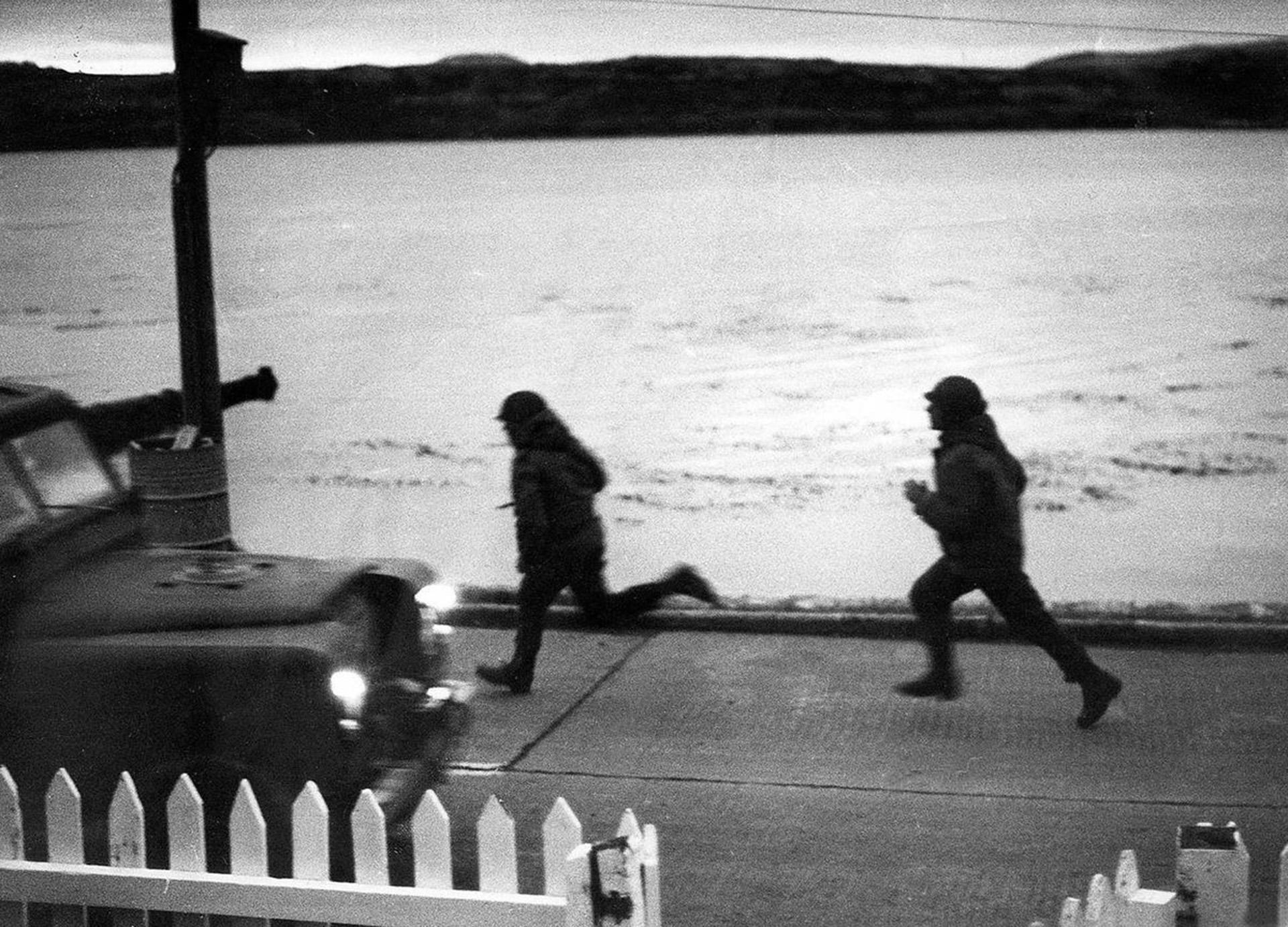 Dos soldados argentinos corren por Ross Road en Puerto Argentinopara ponerse a cubierto de una alerta de bombardeo. 4 de mayo de 1982 (Reuters)