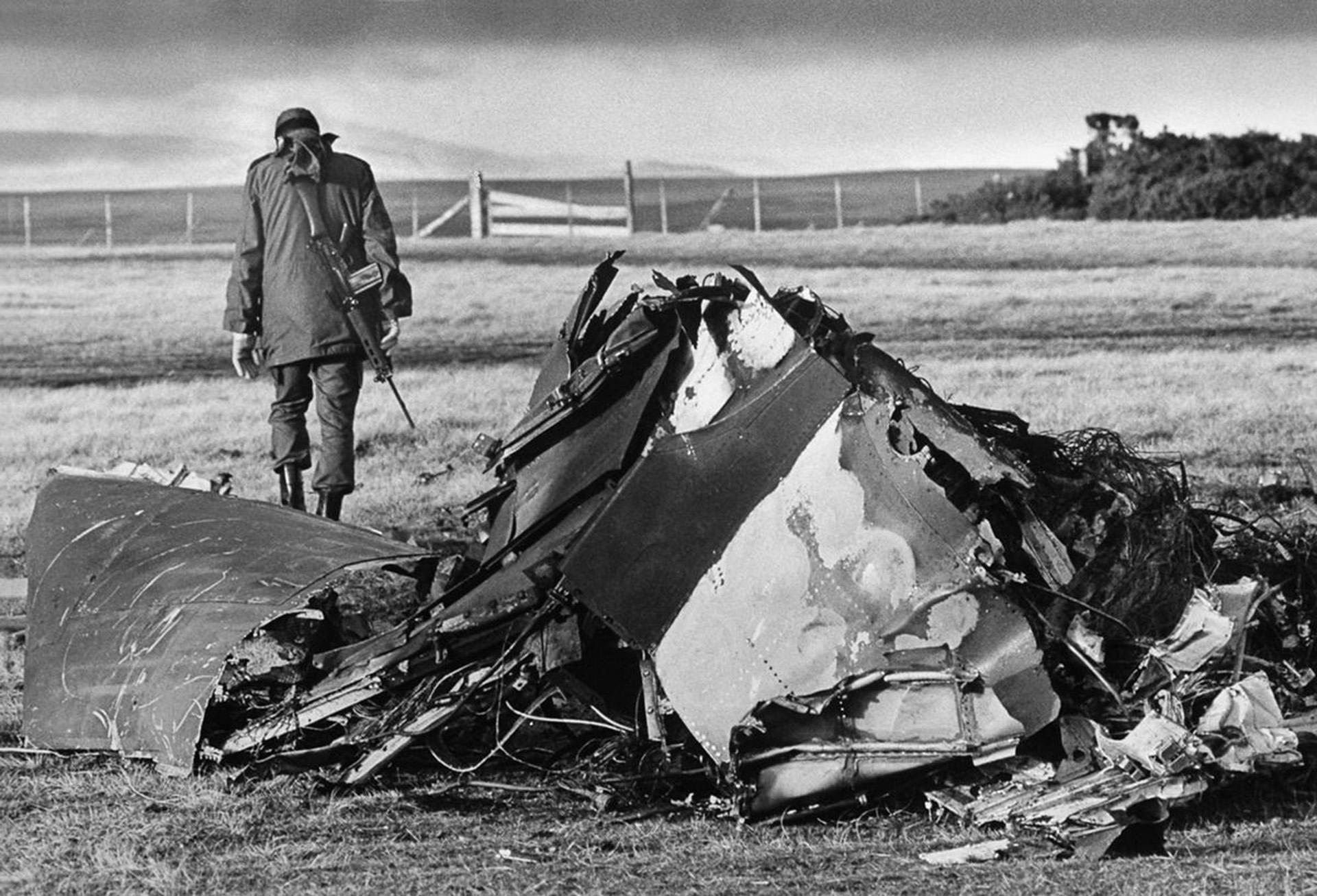Un oficial argentino camina al lado de un avión británico que fue derribado en el puerto de Darwin, ubicado en el itsmo que une el norte y el sur de la isla Soledad, mayo 1982 (Reuters)
