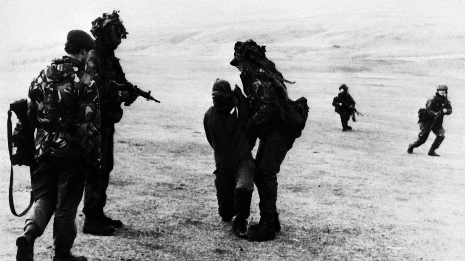 Soldados británicos le tapan la cara a un prisionero argentino por razones de seguridad cuando los ingleses avanzaron sobre Puerto Argentino, el principal puerto y única ciudad de las Malvinas (AP)