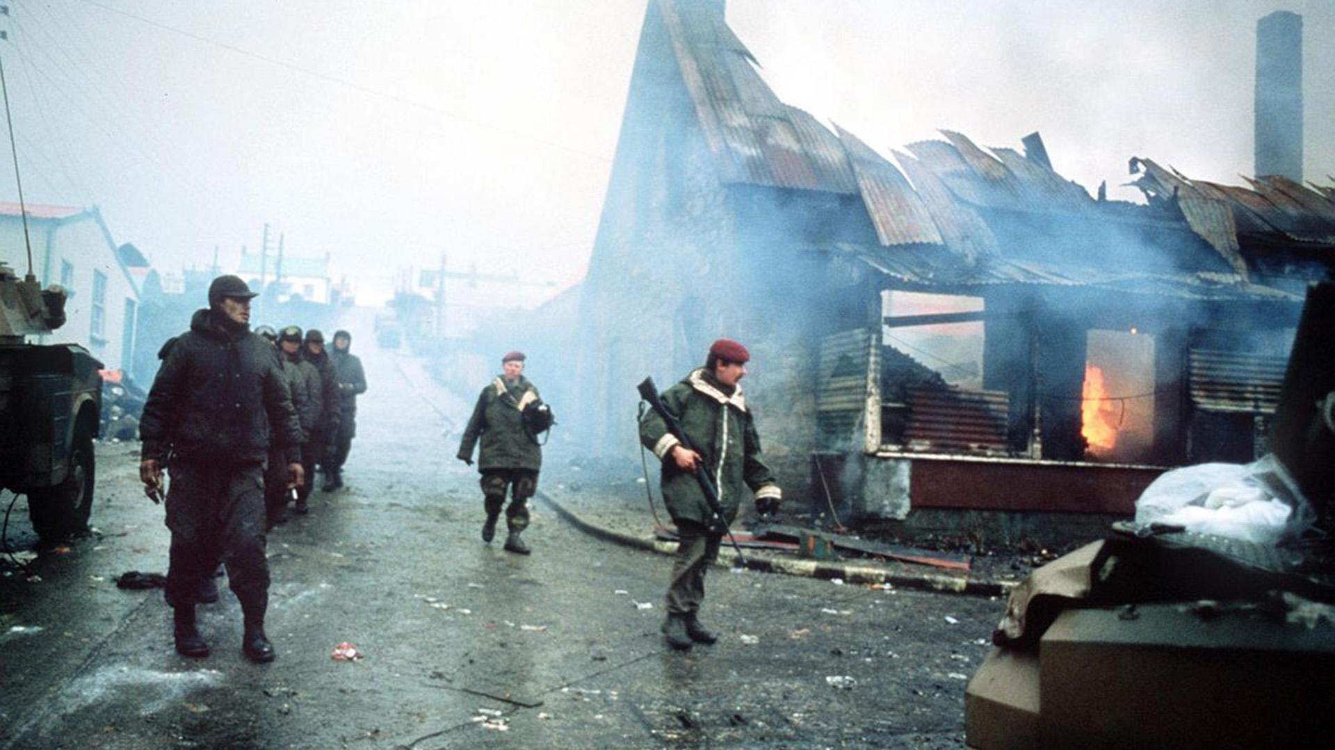 Una fila de prisioneros argentinos camina al lado de un edificio en llamas en Puerto Argentino durante los últimos días de la guerra, en junio de 1982 (AP)