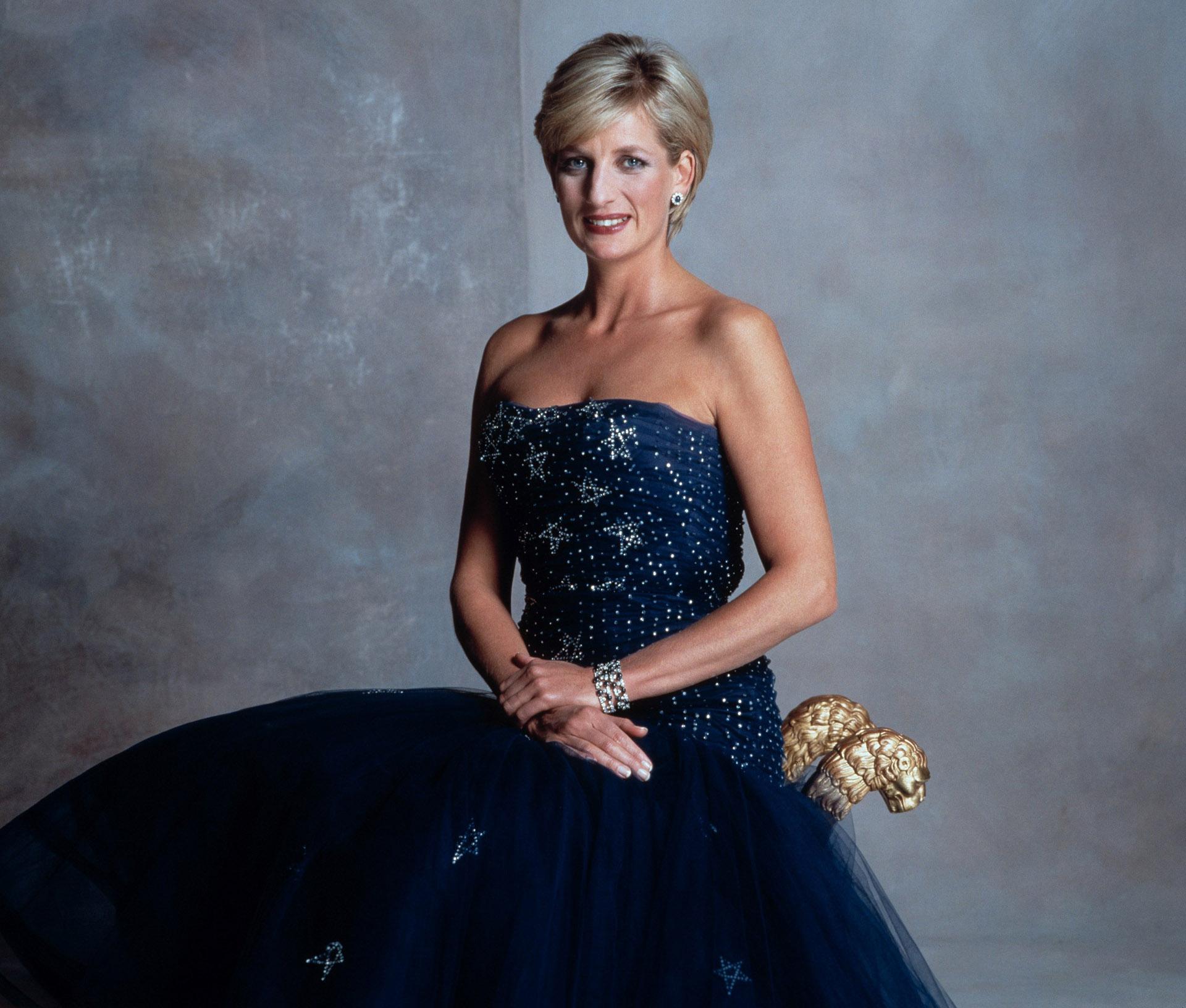 Lady Di, retratada por Mario Testino conun vestido strapless de tul y bordados junto con un brazalete y pequeños pendientes en brillantes con piedras azules