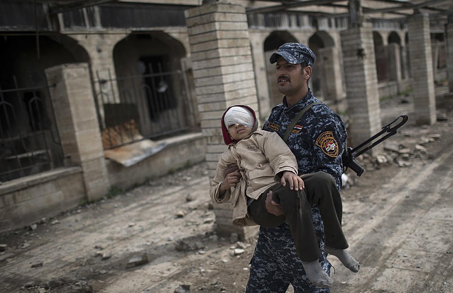 Un militar iraquí carga a un niño herido (AP)