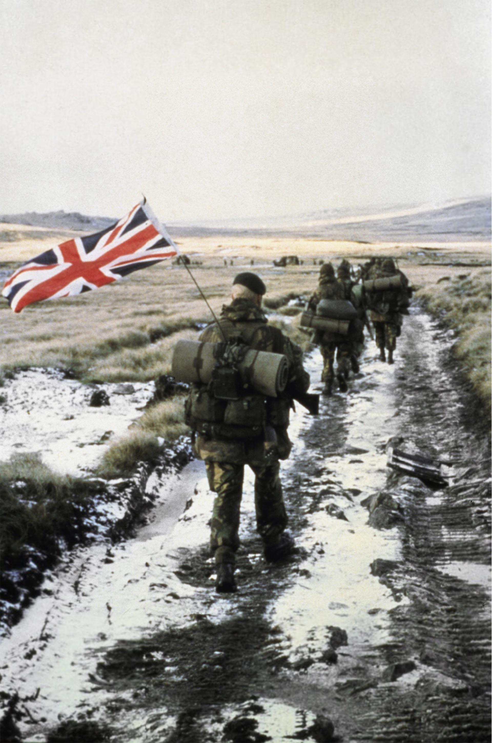 Grupos de los 40 y 45 Comandosde los Royal Marines marchan hacia Puerto ArgentinoEl Marine Peter Robinsonlleva la bandera inglesacomo símbolo de victoria (Imperial War Museums)