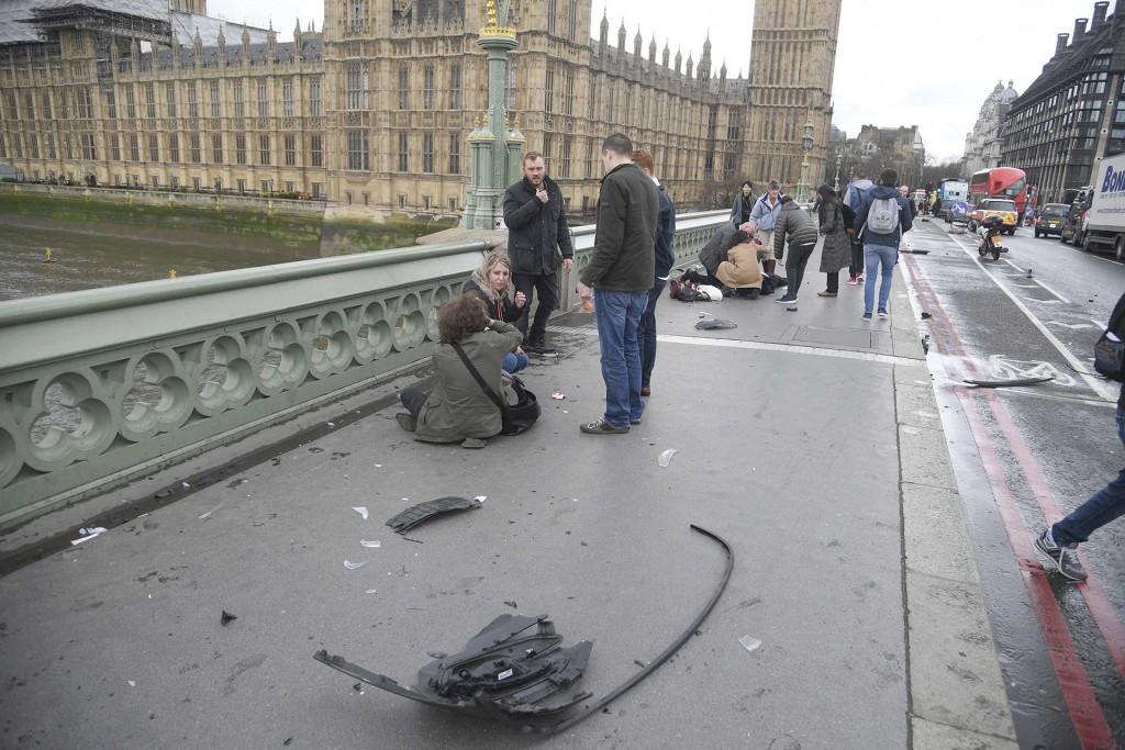 Personas heridas reciben asistencia sobre el Westminster Bridge, frente al Parlamento británico (Reuters)