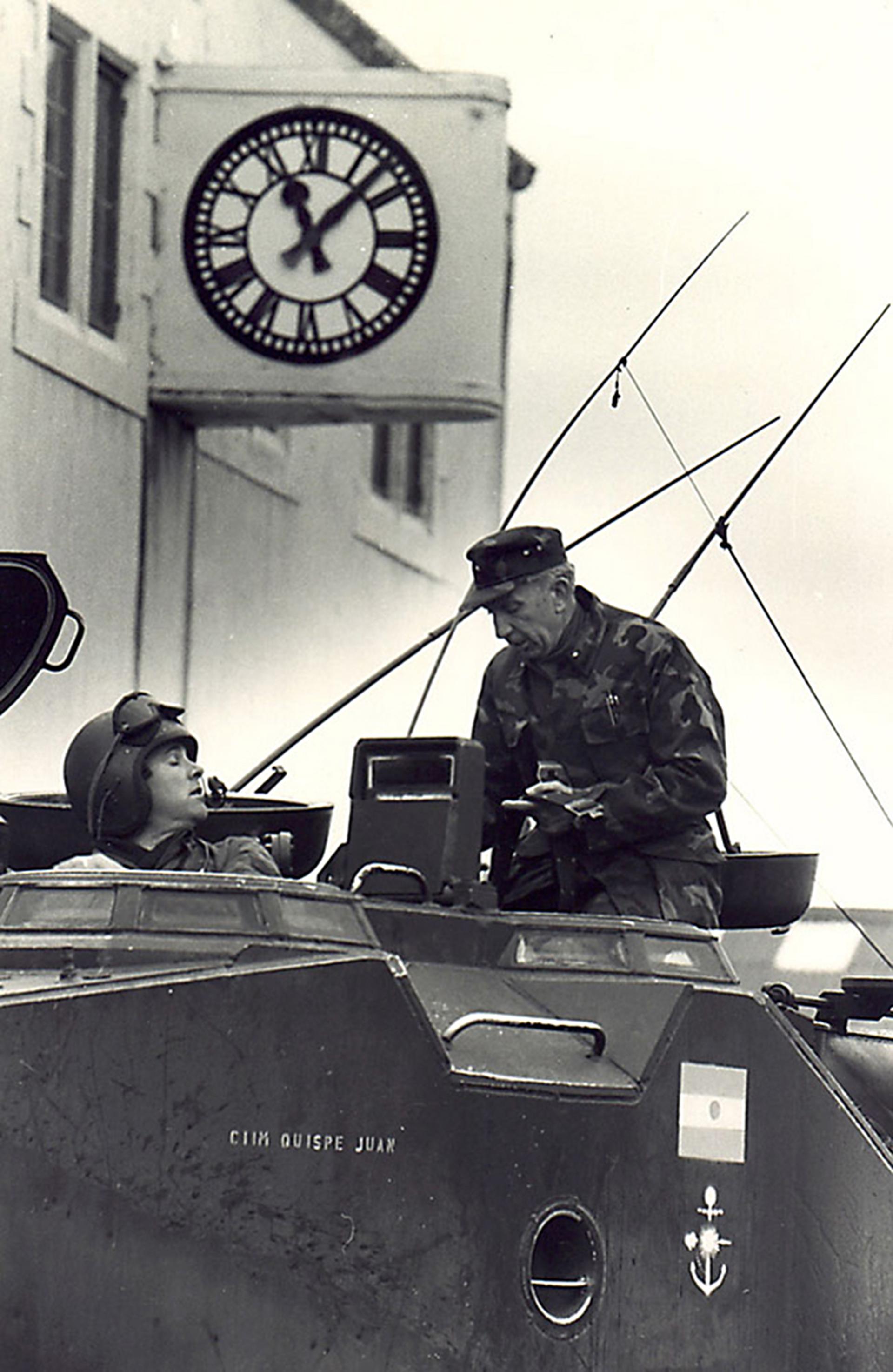 Büsser se asoma por un tanque anfibio estacionado sobre Ross Road en Puerto Argentino, a metros de la casa del gobernador Rex Hunt