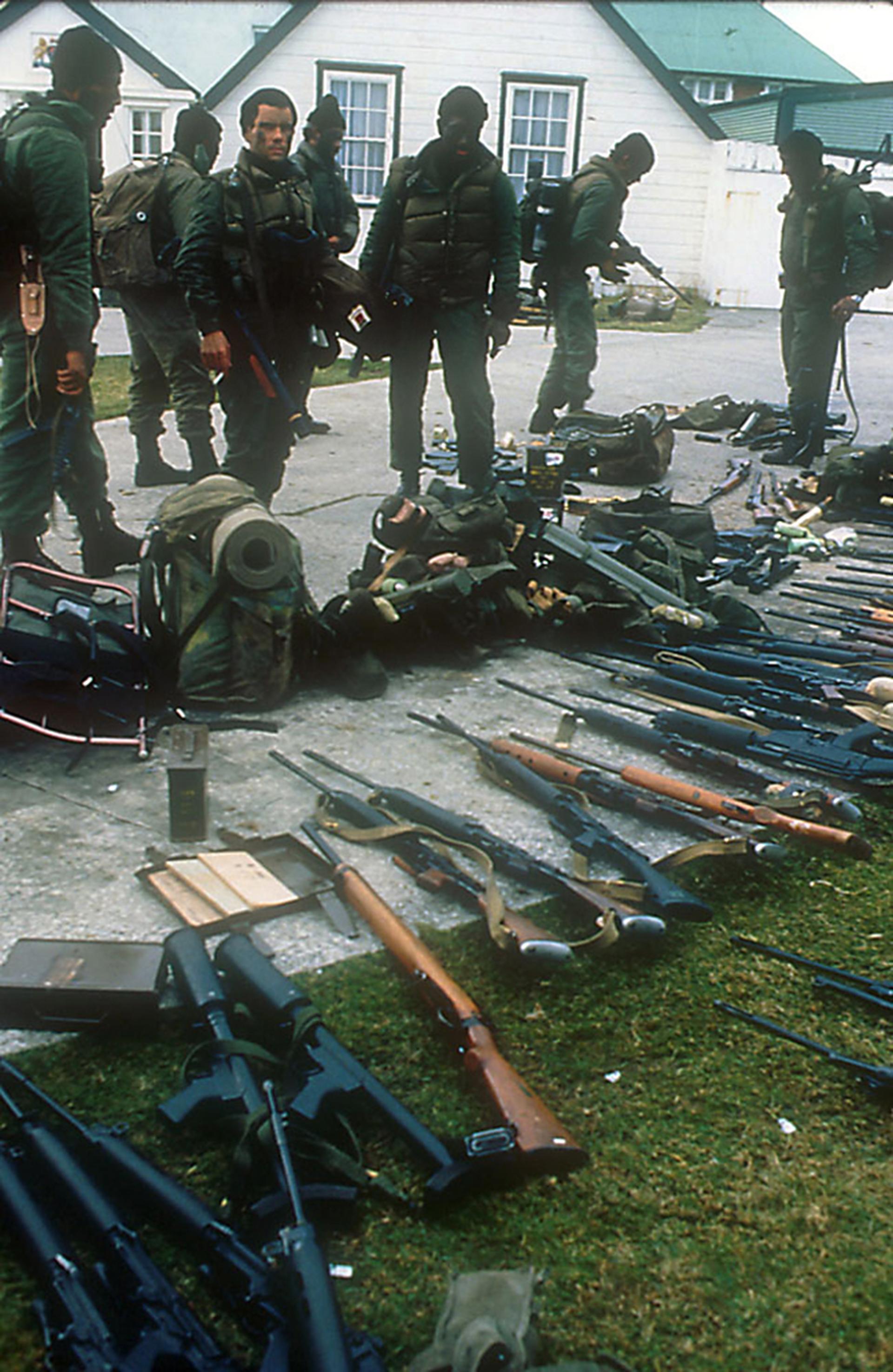 Los comandos argentinosrecolectan las armas de lossoldados británicos y las juntan a un costado de la casa de Hunt, durante la larga mañana del 2 de abril