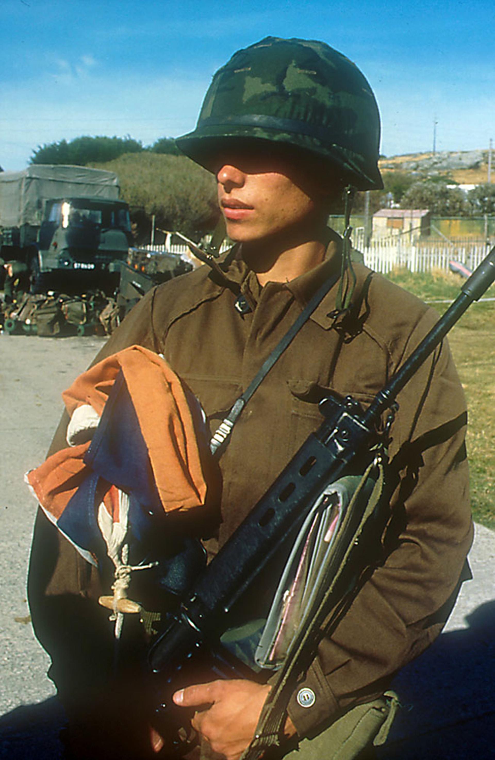 El comandante Büsser da la orden de quitar del mástil de la casa del gobernador Hunt la bandera del Reino Unido, que es custodiada como trofeo de guerra por un soldado argentino