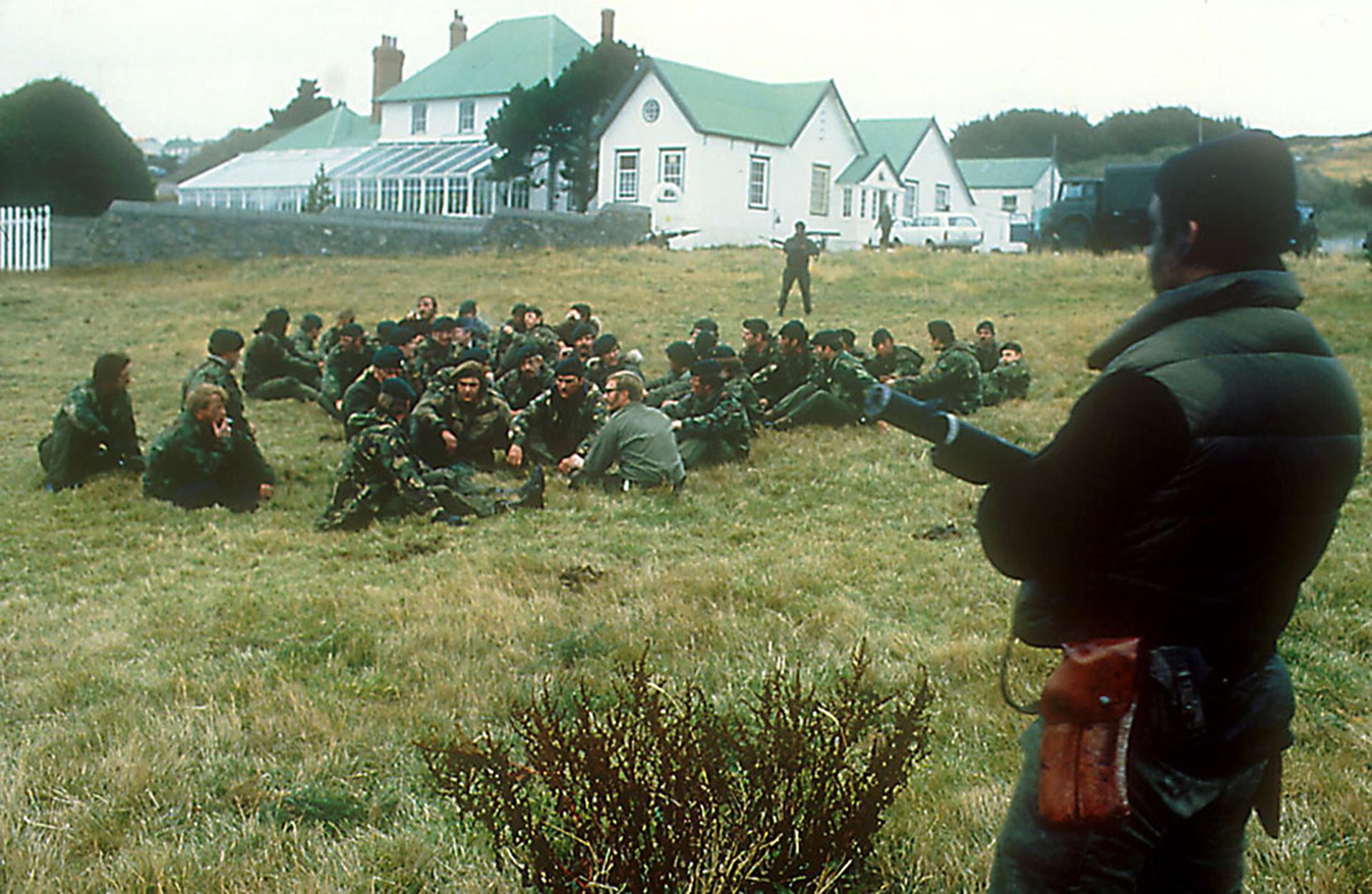 Tras la rendición, los anfibios argentinos llevana los Royal Marineshasta los jardines ubicados frente a la casa del gobernador Rex Hunt, quien se resistió a dejar su residencia