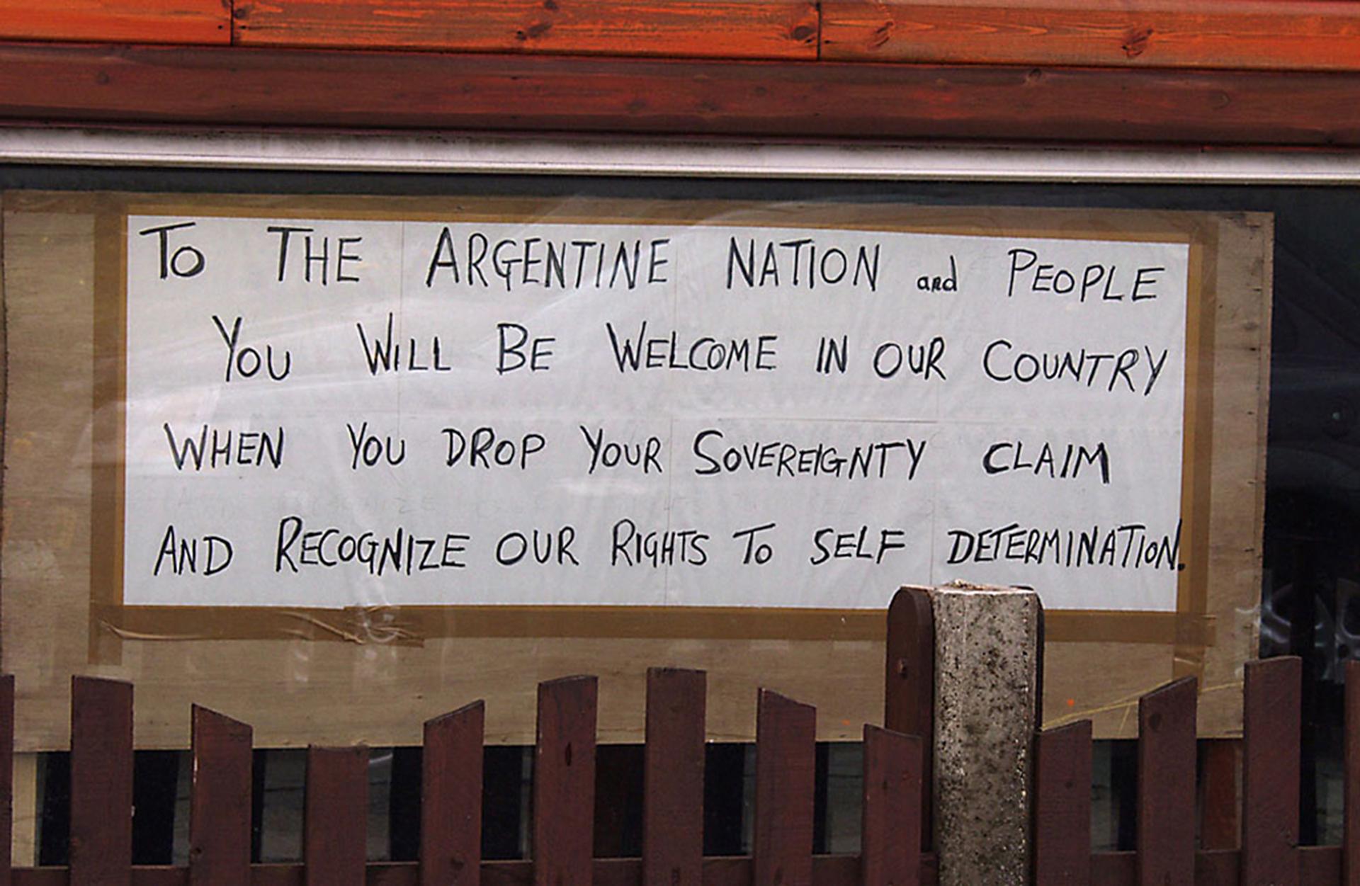 """Antes del 2 de abril, un vuelo semanal conectaba el continentecon Malvinas. La relación era respetuosa pero no cordial. En el aeropuerto, este cartel pegado por los isleños advertía: """"Serán bienvenidos a nuestro país cuando dejen caer su reclamo de soberanía y reconozcan nuestros derechos a la autodeterminación"""""""