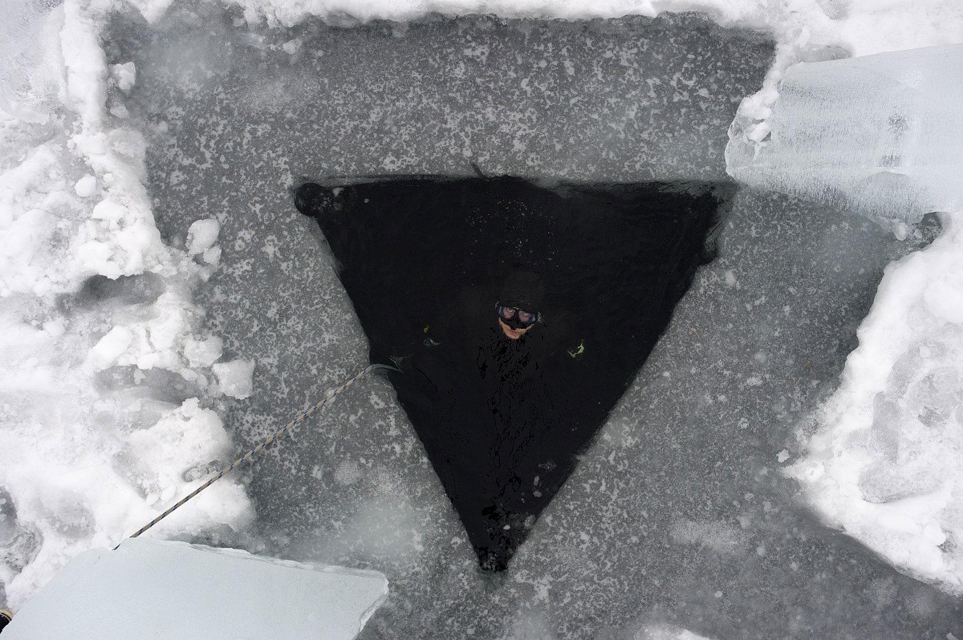 El agujero triangular que deben taladrar para bucear bajo hielo (AFP)