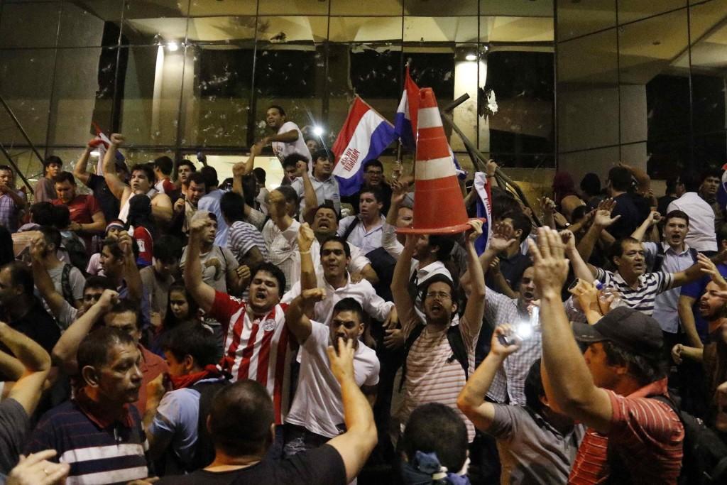 Manifestantes gritan consignas afuera de la sede del Congreso Nacional en Asunción