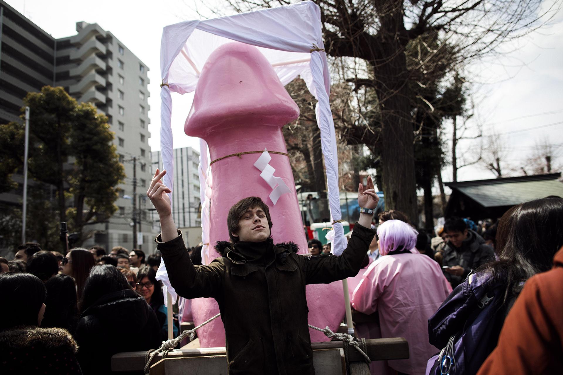 Un hombre posa al lado de un gran monumento fálicodurante el Festival de Kanamara, anual, en Kawasaki. el 2 de abril de 2017 (AFP)