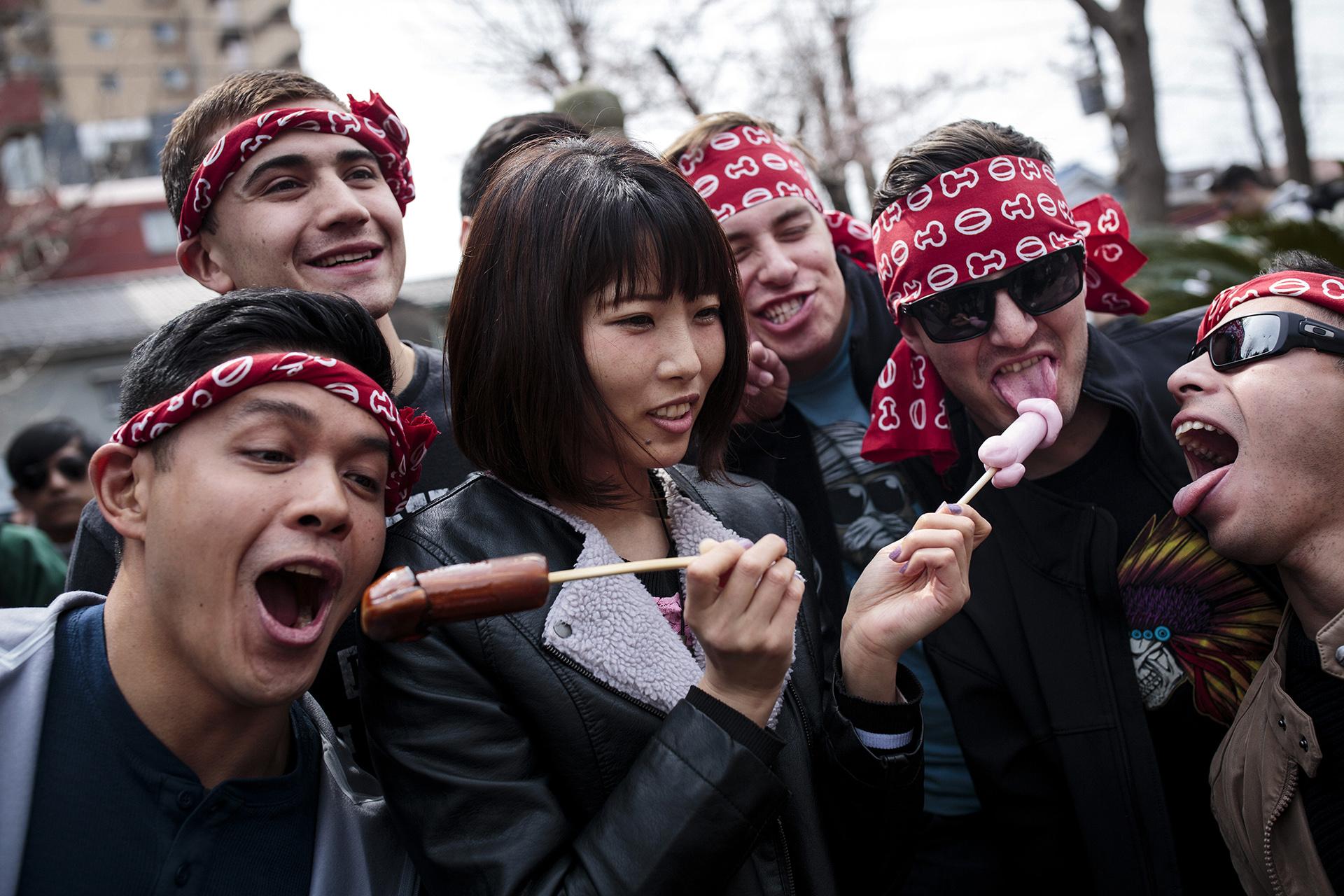 Una mujer posa junto a otros hombres con caramelos en forma de pene (AFP)