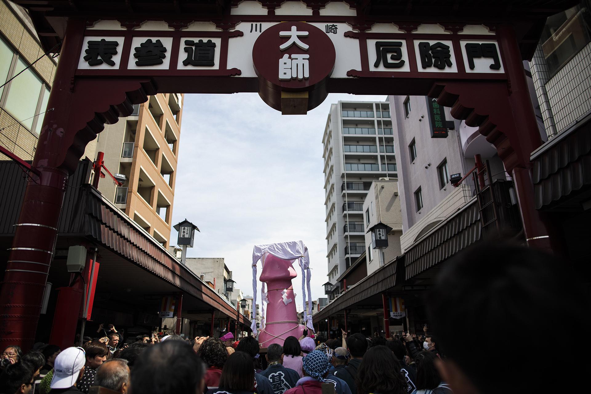 Gente carga un gran monumento fálico durante el Festival del Pene de Acero en Kawasaki (AFP)