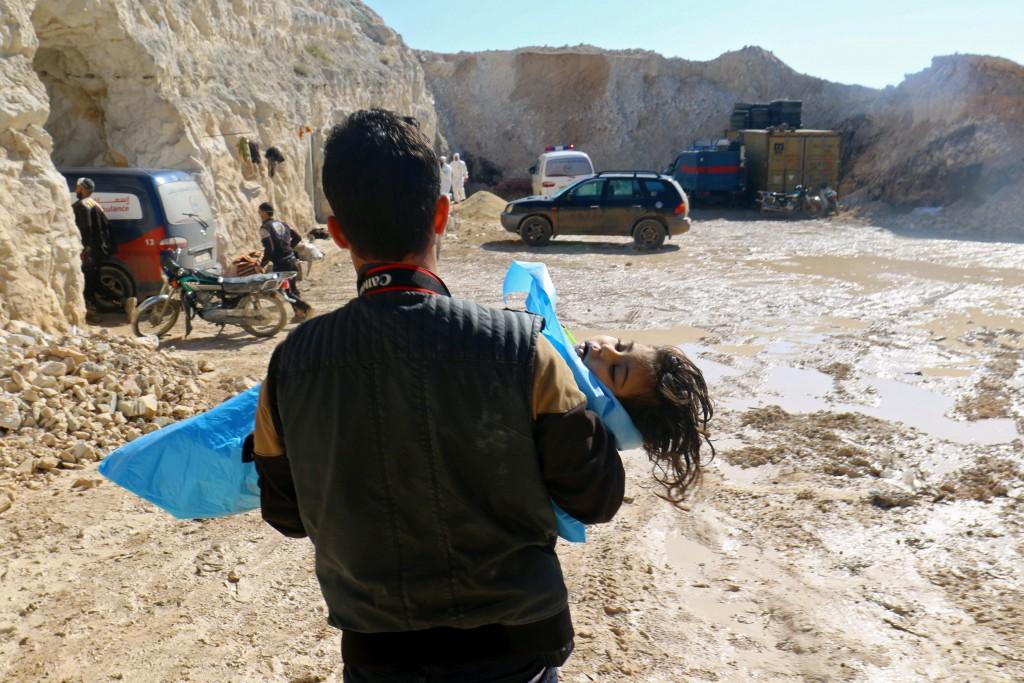 Un hombre carga el cádaver de una niña tras el ataque químico (Reuters)