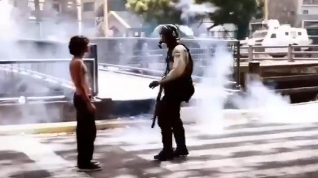 Esta imagen lo dice todo: un joven protesta desarmado, y es reprimido por un militar chavista