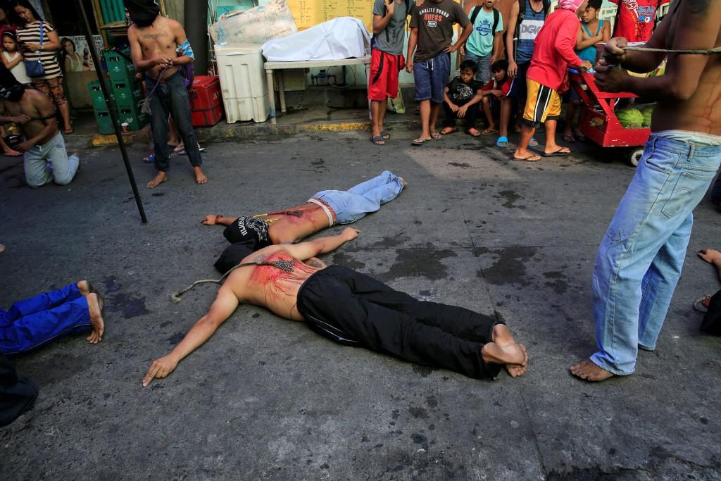 Boca abajo y cubiertos por una máscara, los penitentes simulan con sus brazos la crucifixión (Reuters)
