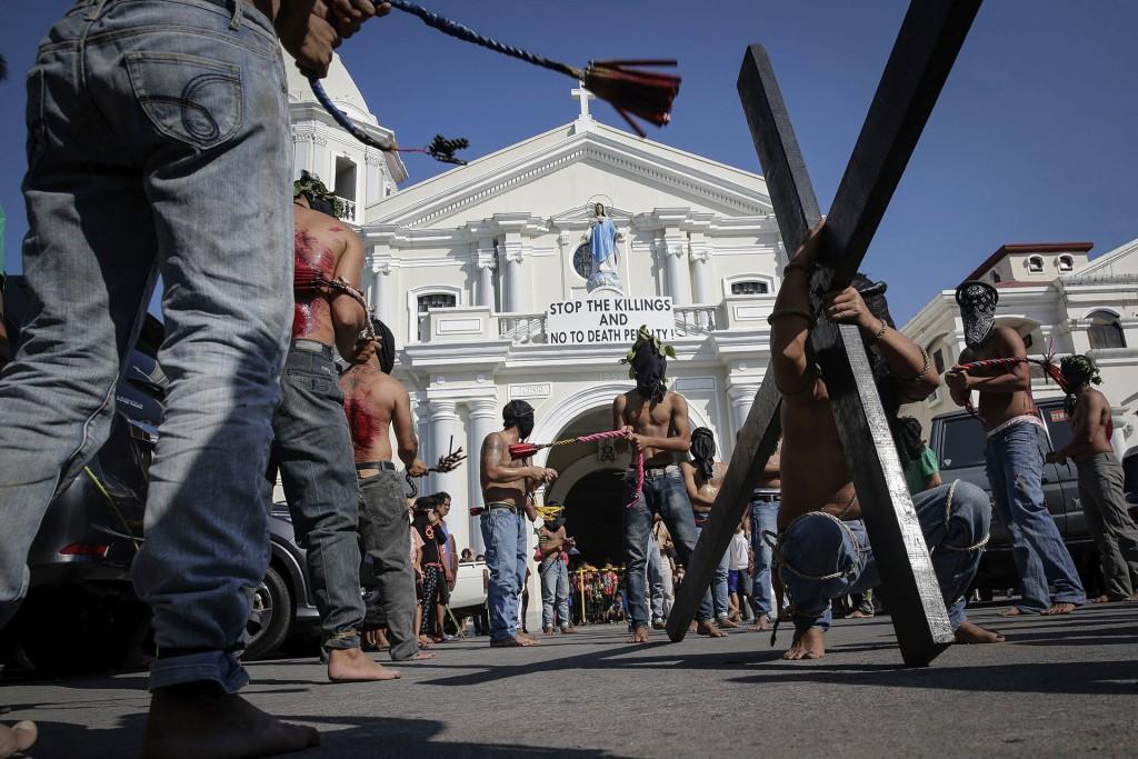"""En San Fernando, un hombre lleva su propia cruz rodeado de penitentes que se golpean a sí mismos con sus látigos y frente a un cartel en contra de la agresiva política del gobierno filipino contra el crimen: """"Paren los asesinatos, no a la pena de muerte"""" (EFE)"""