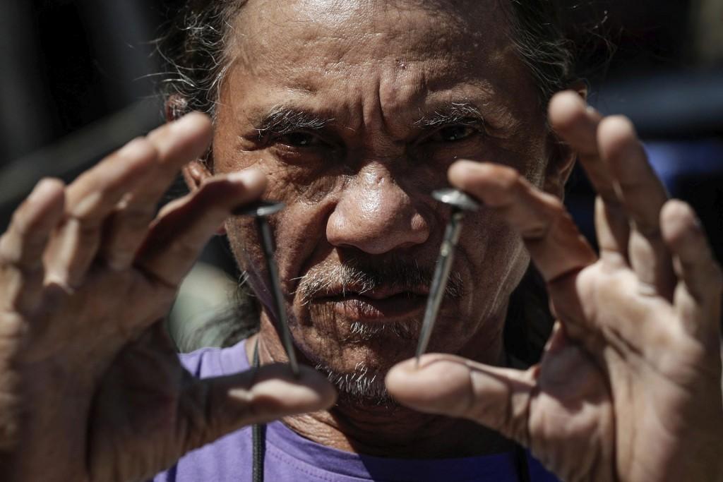 Rubén Enaje, un penitente filipino, muestra dos clavos que se utilizarán para clavarlo a una cruz (EFE)