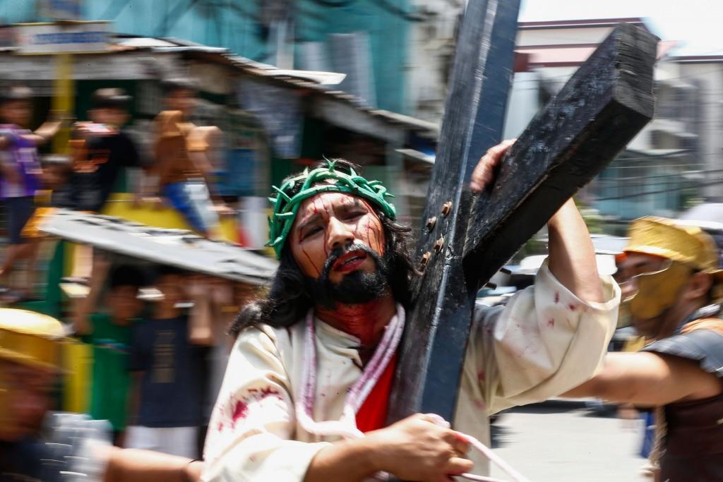 Gerardo Galvez Jr como Jesucristo lleva su cruz entre la muchedumbre(EFE)