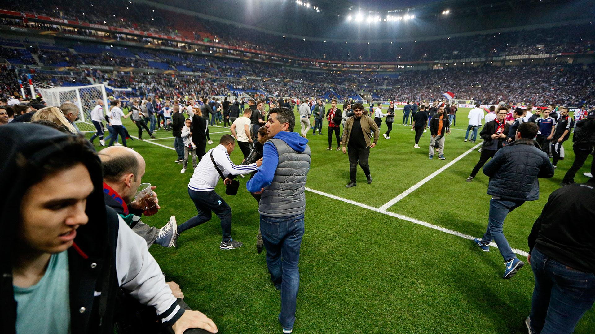 Los seguidores del Lyon escaparon de las bengalas e invadieron el campo de juego (Reuters)