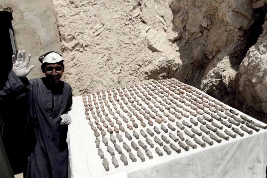 """Un hombre saluda junto a estatuillas """"ushabti"""" descubiertas. Los descubrimientos realizados en la cámara de la parte occidental serán revelados más adelante, ya que las excavaciones aún no han sido concluidas (EFE)"""