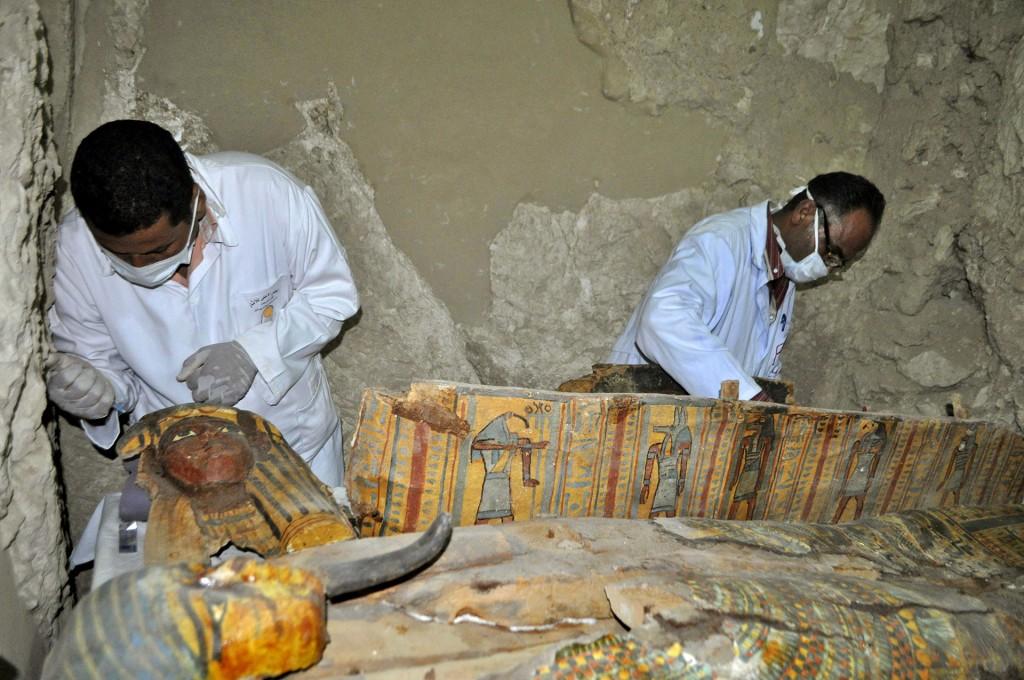 """Arqueólogos trabajan en un sarcófago de madera. El ministro de Antigüedades, Jaled al Anani, dijo a la web del diario oficial Ahram que, aunque la tumba es pequeña, se trata de un """"descubrimiento importante"""" porque la colección funeraria está prácticamente intacta (AFP)"""