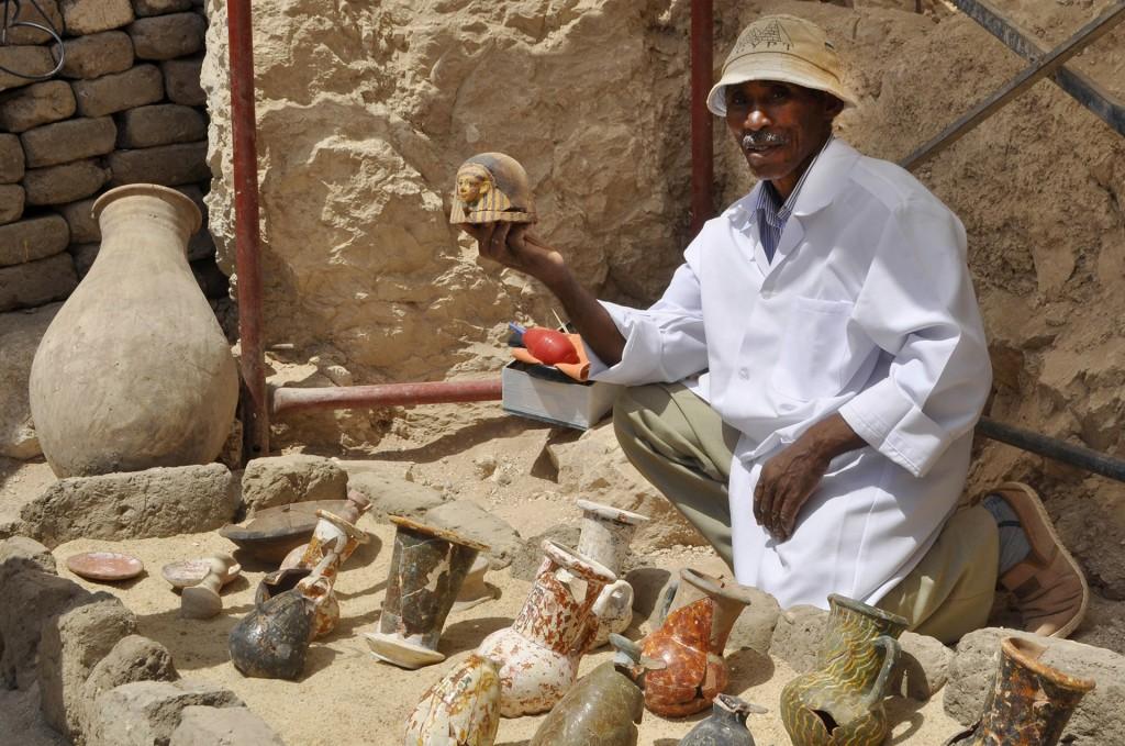 """Un miembro del equipo arqueológico muestra los descubrimientos en la tumba. El mausoleo fue hallado en la zona de Dra Abu al Naga, ubicada en la orilla occidental del Nilo, y pertenece a un alcalde llamado Ausrihat. Aseguran que están """"casi intactas"""""""