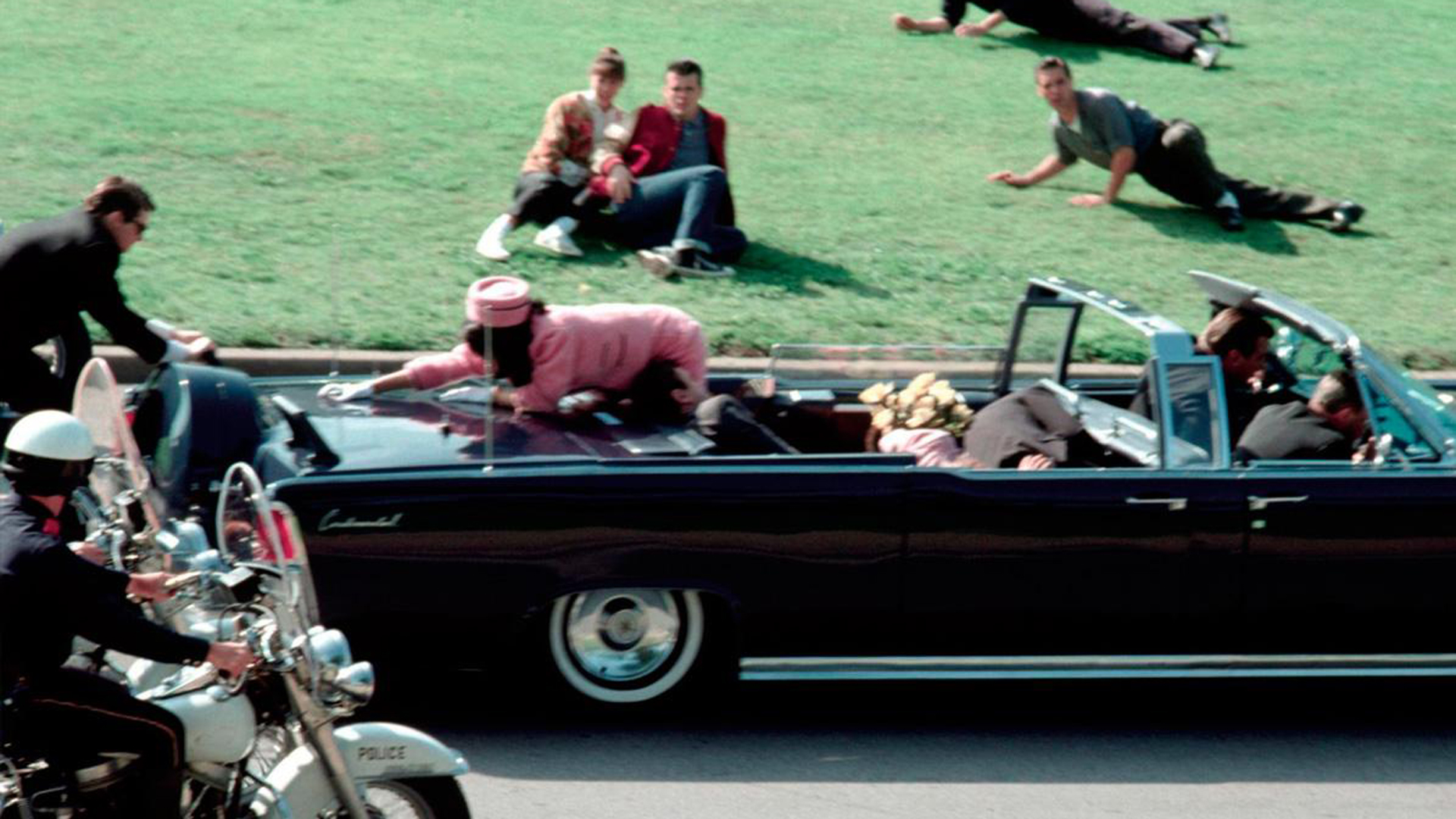 Otra imagen de John F. Kennedy a bordo de su automóvil convertible. En la imagen puede verse cómo Clint Hill -el guardaespaldas del presidente- comienza a subirse al Lincoln en el que iban el mandatario y la primera dama, Jackie Kennedy