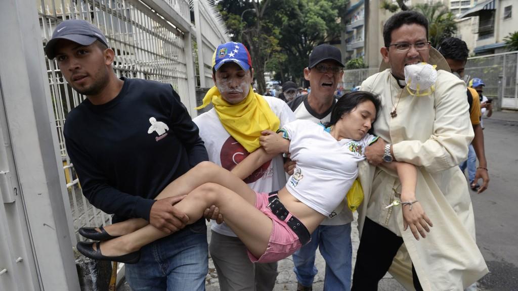 Una mujer que fue afectada por la represión es trasladada en Caracas (AFP)
