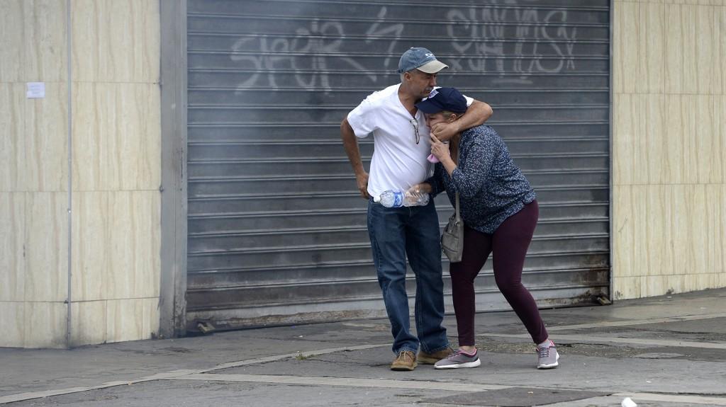Una pareja intenta protegerse entre los gases lanzados por las fuerzas represivas