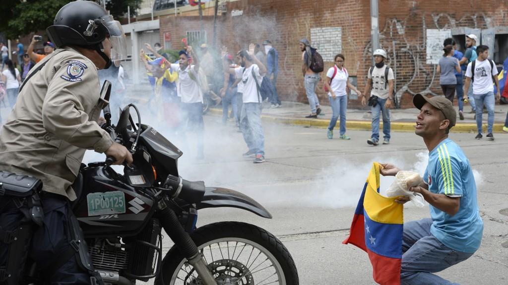 Un activista se enfrenta a un policía con la bandera venezolana en manos, rodeados por gases lacrimógenos en Caracas (AFP)
