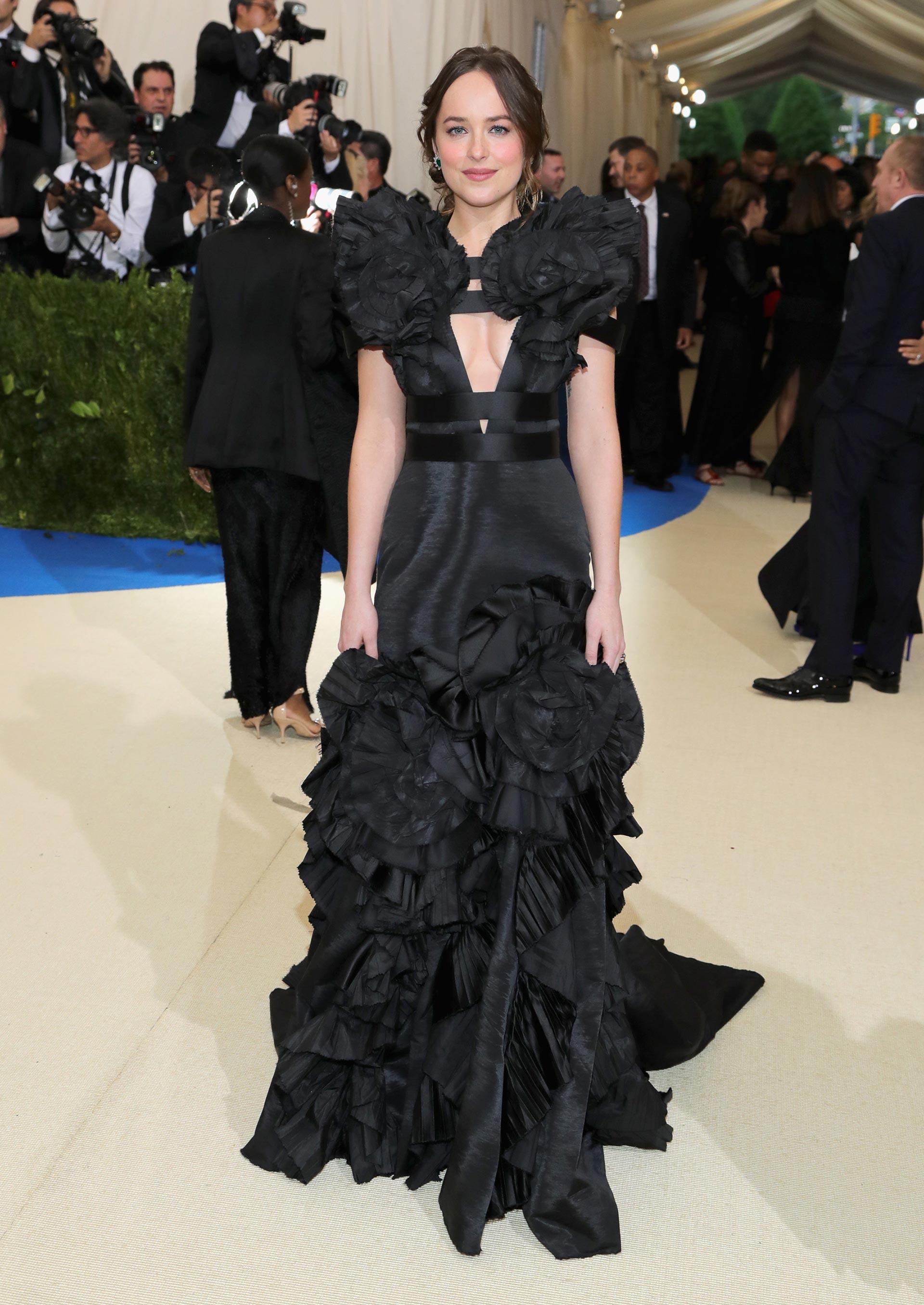 Dakota Johnson optó por un vestido oscuro de Gucci, alusivo a 50 Sombras de Grey al igual que al estilo del modisto homenajeado (Getty Images)