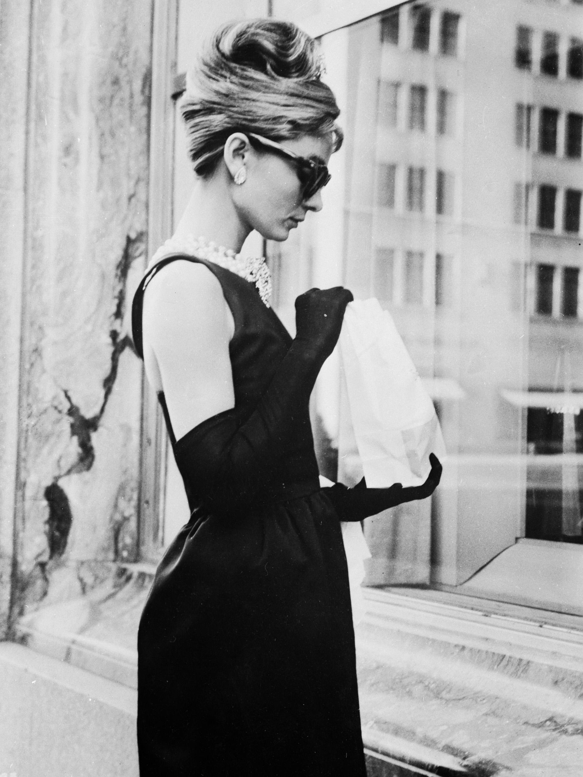Audrey Hepburn filamando 'Desayuno en Tiffany' en 1961, un film que la catapultó a la fama internacional. Su look: el famosos vestido negro de Givenchy con su collar de perlas y anteojos cat eye, quedó instalado en la moda (Keystone Features/Getty Images)