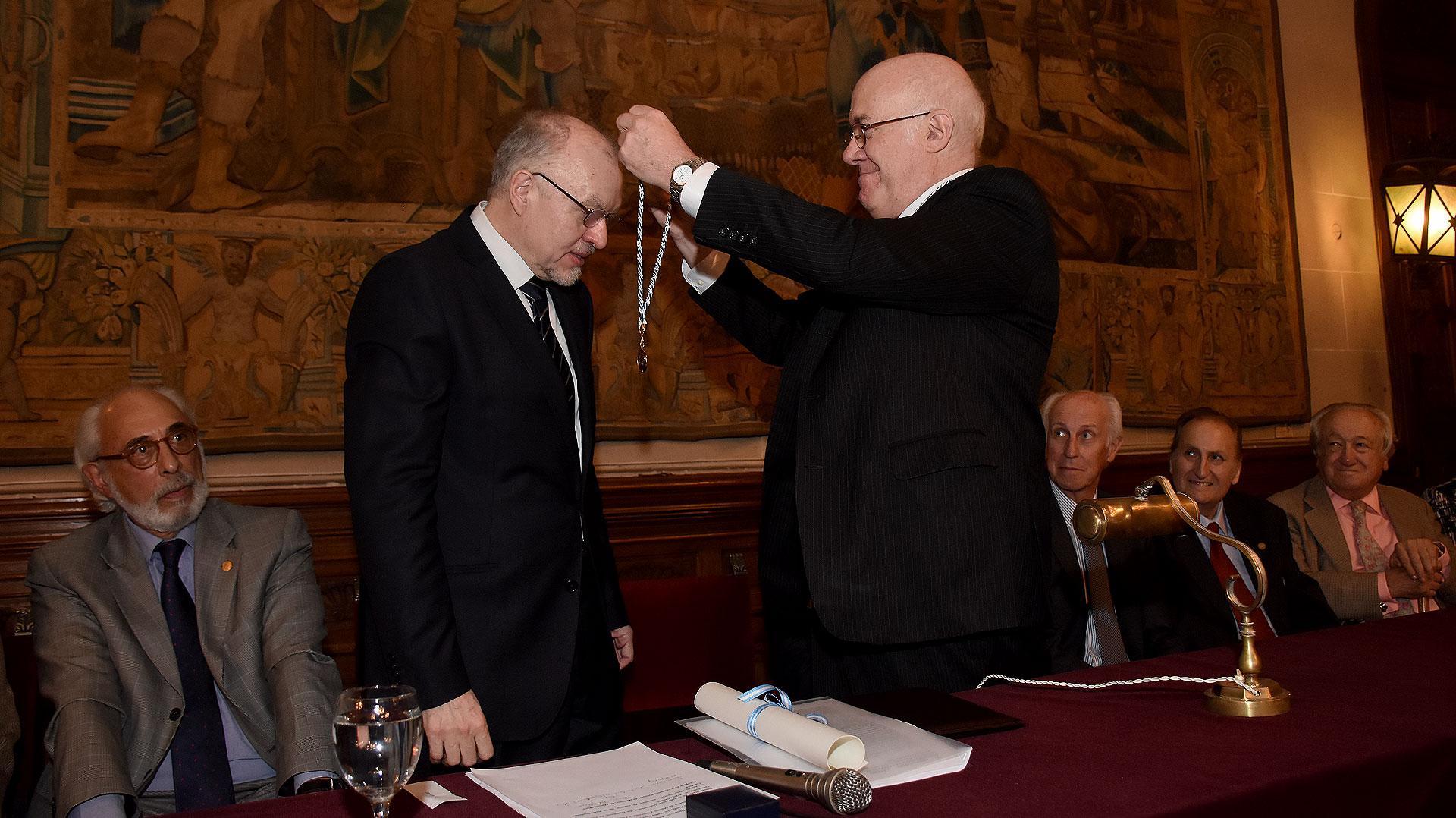 José Luis Moure, presidente de la Academia Argentina de Letras, le coloca la medalla honorífica