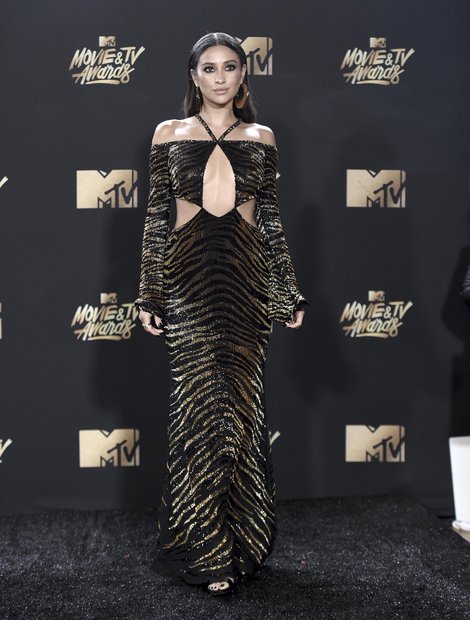 Shay Mitchell brilló en la pasarela con un vestido imponente en negro con escote y detalles en dorado (Richard Shotwell/Invision/AP)