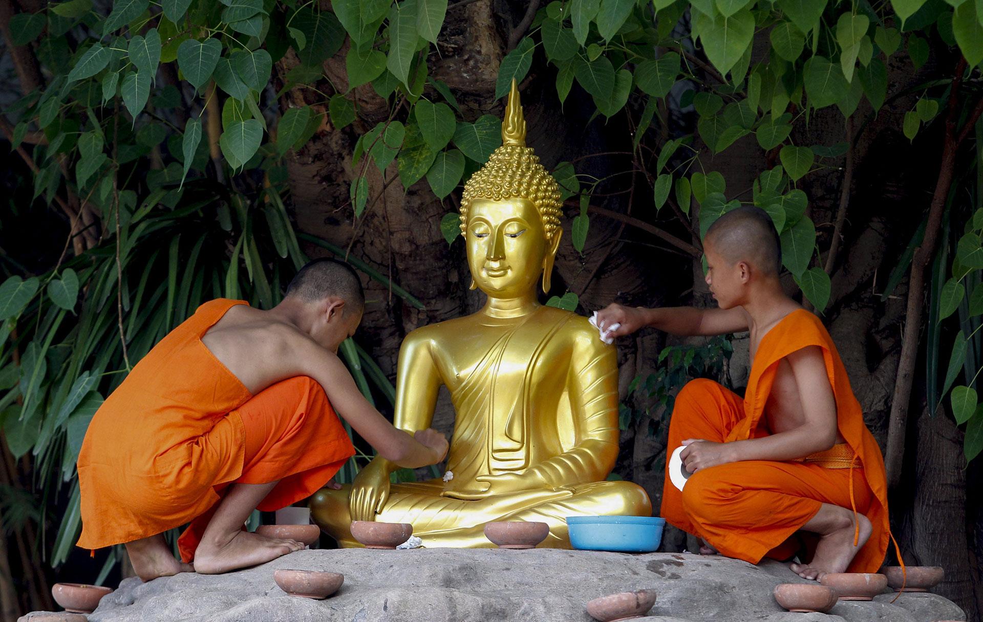 Dos monjes budistas limpian una escultura de Buda durante una ceremonia religiosa para celebrar el Día de Buda en la provincia de Chiang Mai (Tailandia) el 10 de mayo de 2017. (EFE)