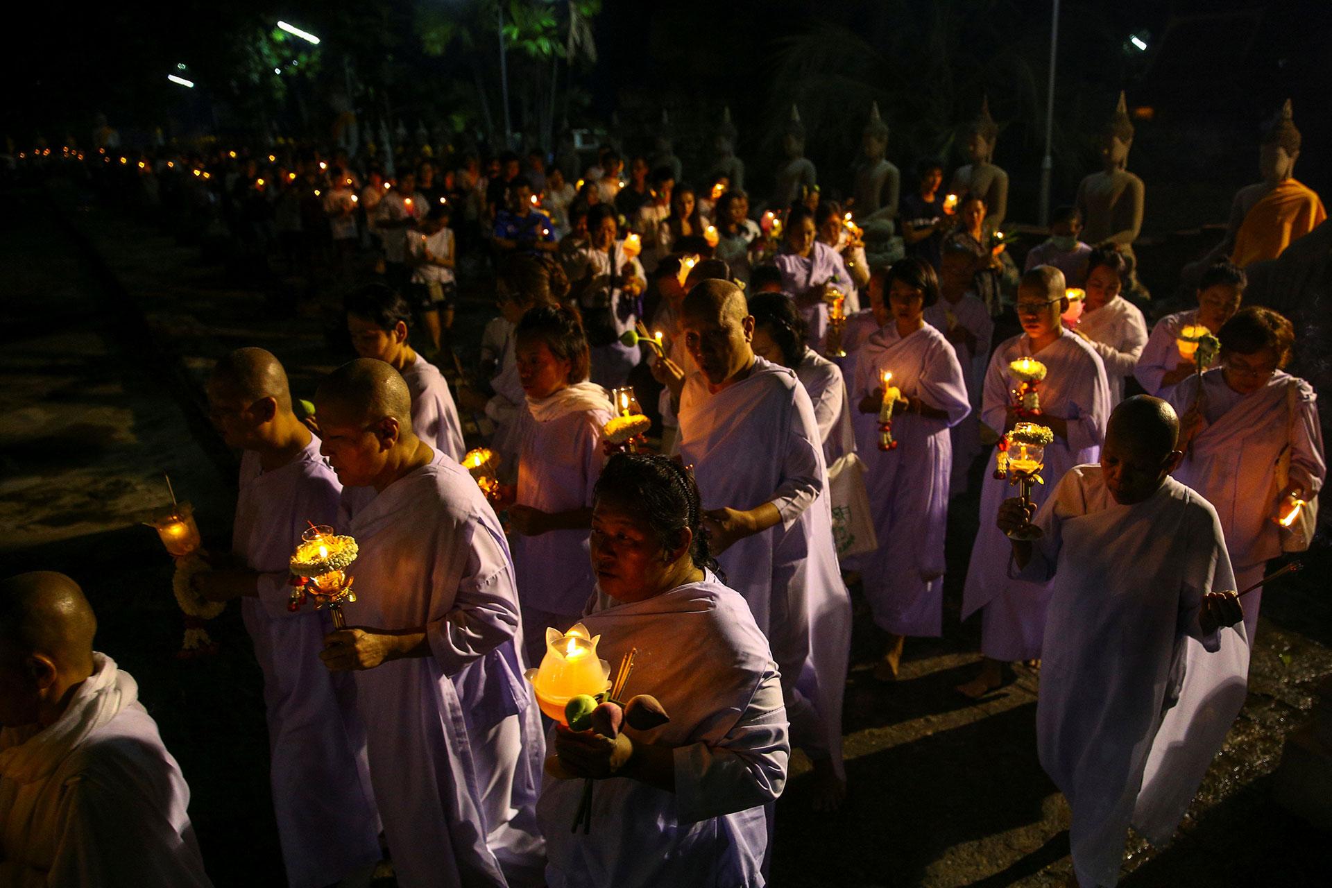 Monjas y monjes budistas cargan velas mientras rezan en el templo Chai Mongkhon en Ayutthaya, Tailandia el 10 de mayo de 2017. (Reuters)