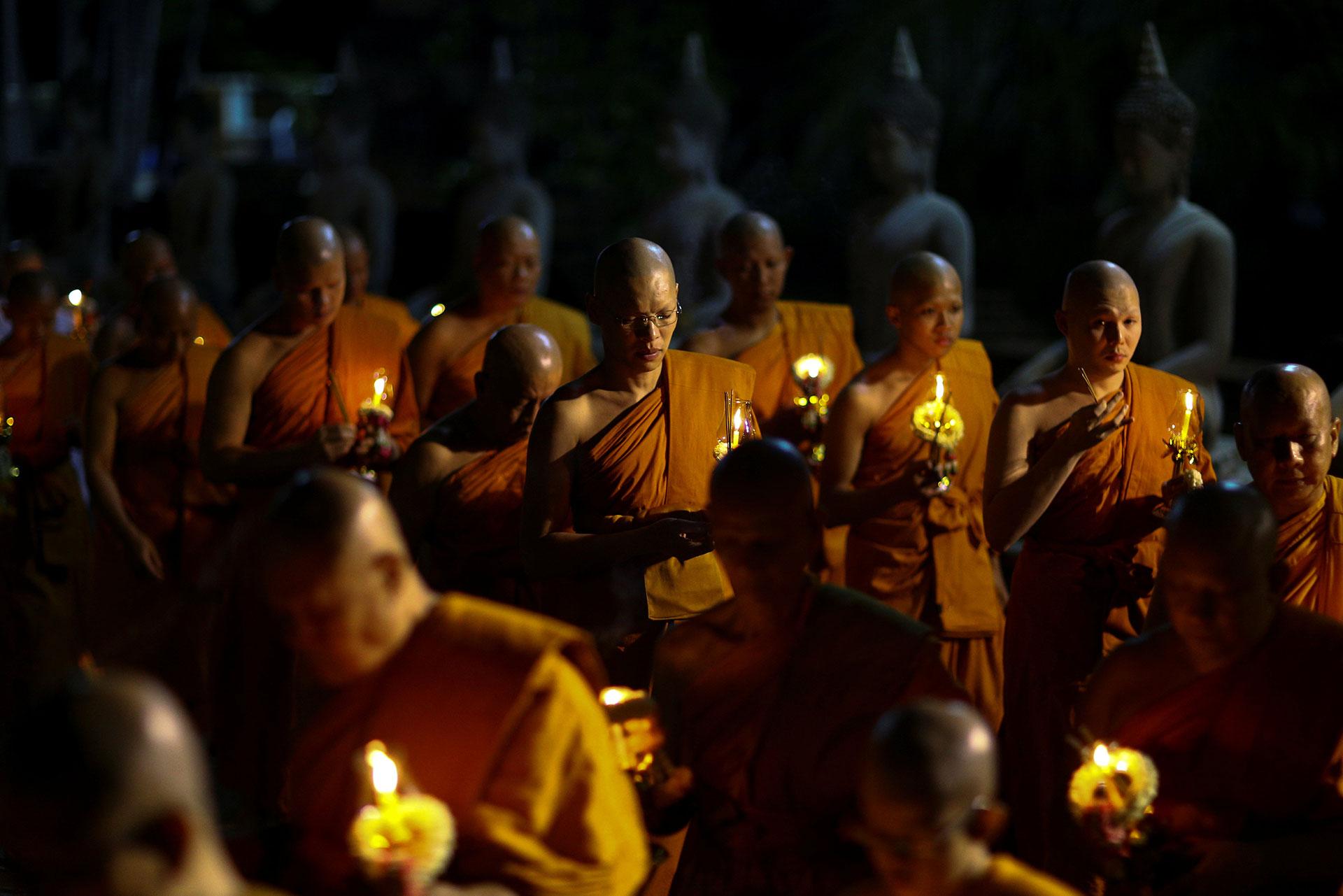 Monjes budistas cargan velas mientras rezan en el templo Chai Mongkhon en Ayutthaya, Tailandia el 10 de mayo de 2017. (Reuters)