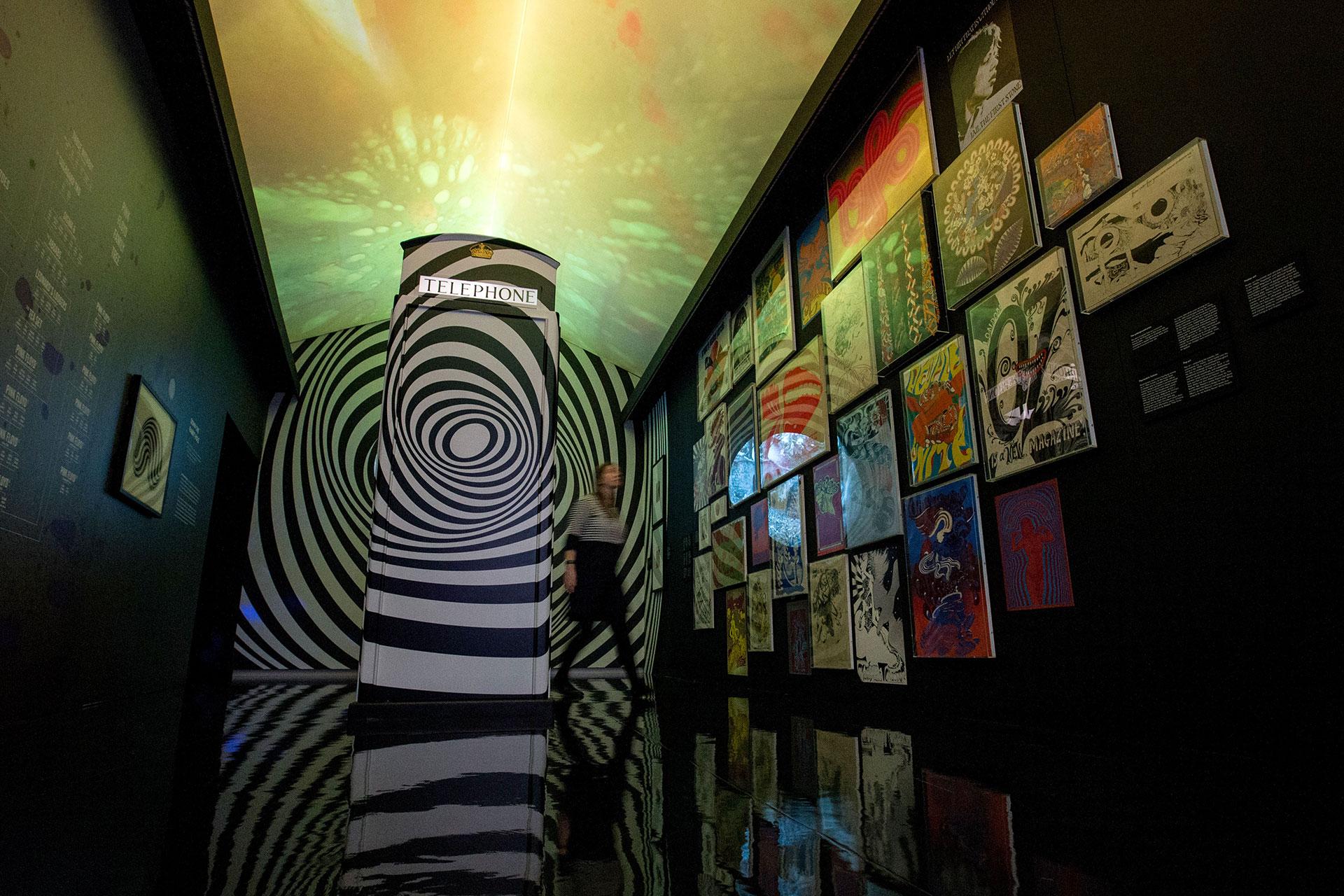 Una cabina telefónica inspirada en el UFO club de Londres junto a pinturas del artista inglésBridget Riley (AFP)