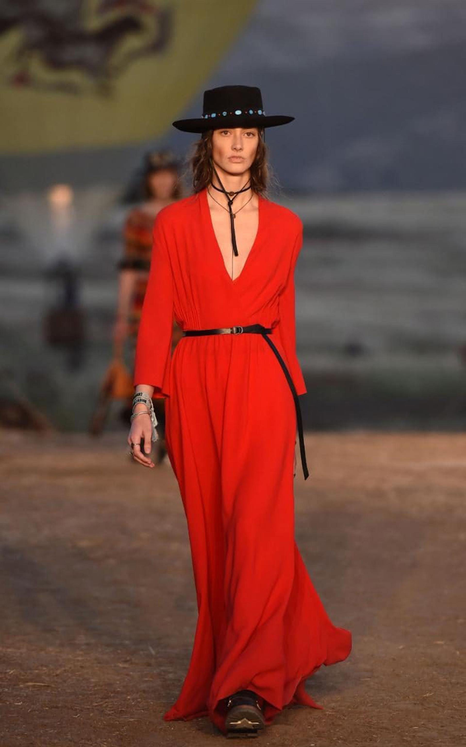 Sombrero panamá plato con piedras turquesa y un vestido rojo con mangas y escote pronunciado presentado con cinturón a la cintura y borcegos (AFP)