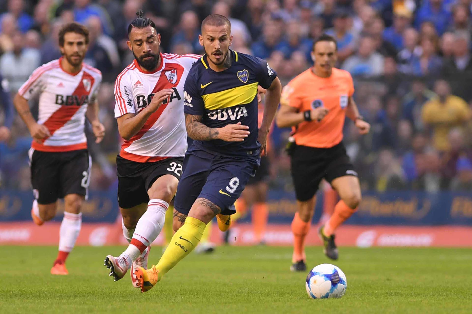 Darío Benedetto se escapa con la pelota, Ariel Rojas corre al acecho