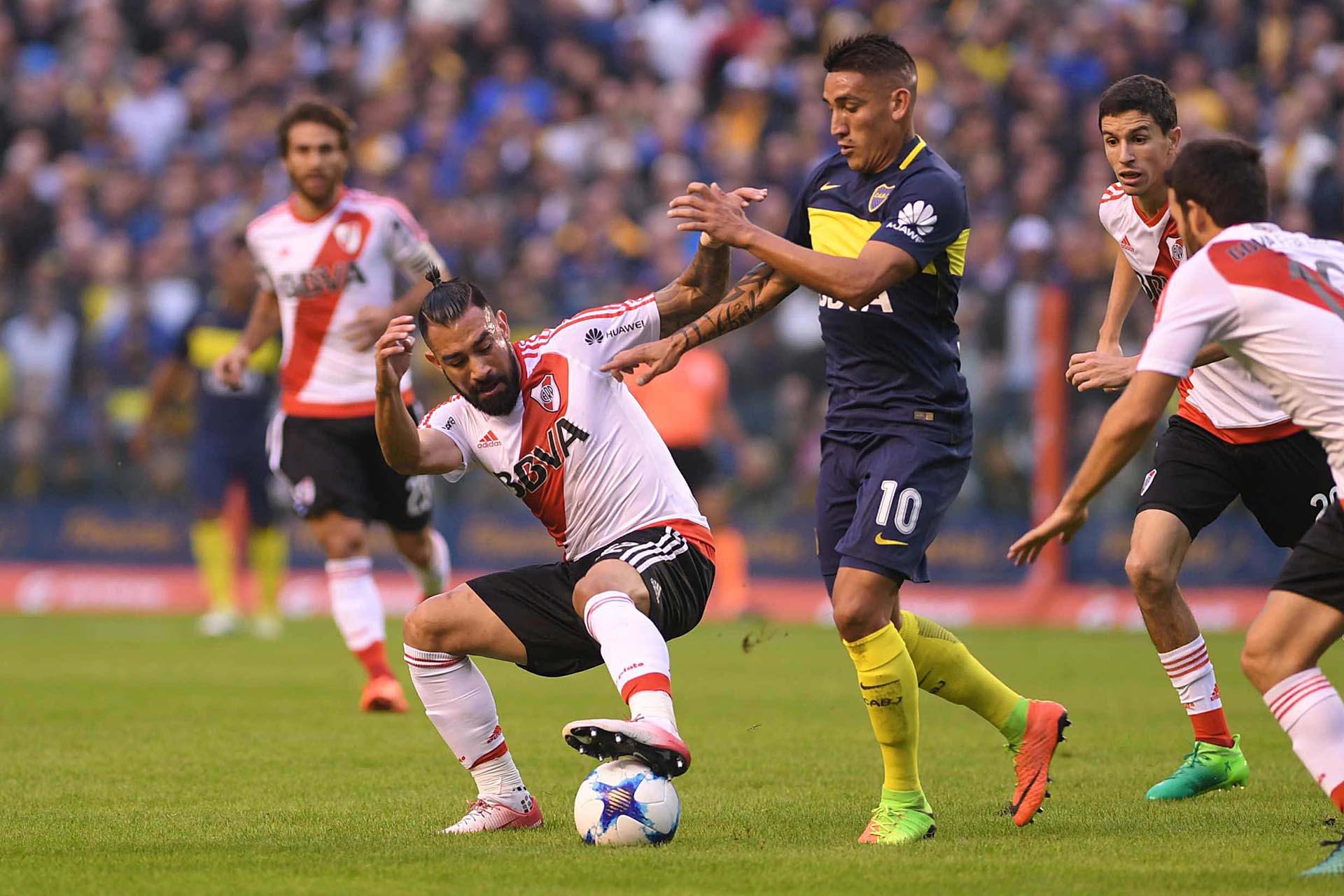 Ariel Rojas retiene la pelota ante el acecho de Ricardo Centurión