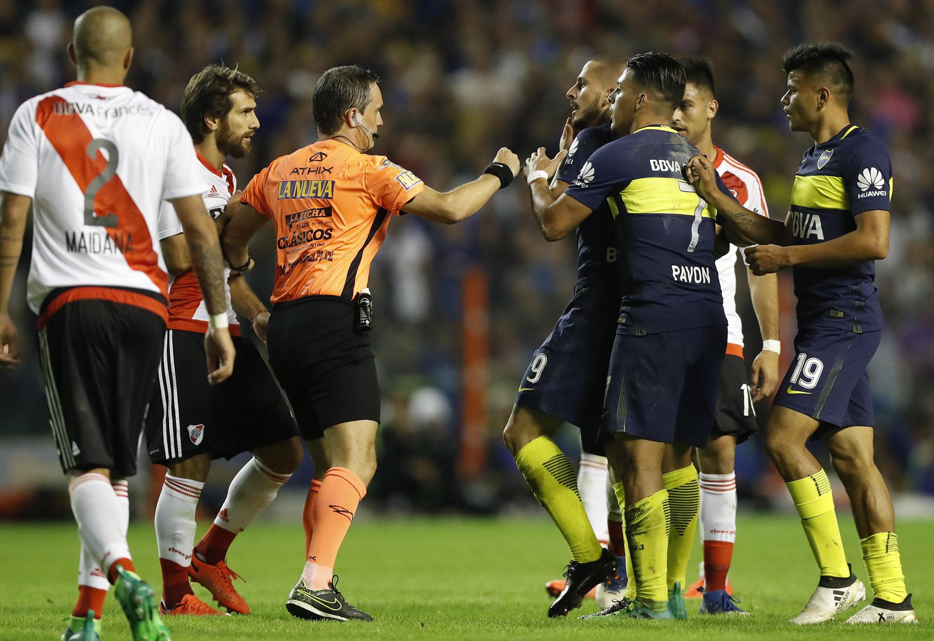 El arbitro Patricio Lousteau reprende al jugador de Boca Dario Benedetto, mientras sus compañeros lo contienen