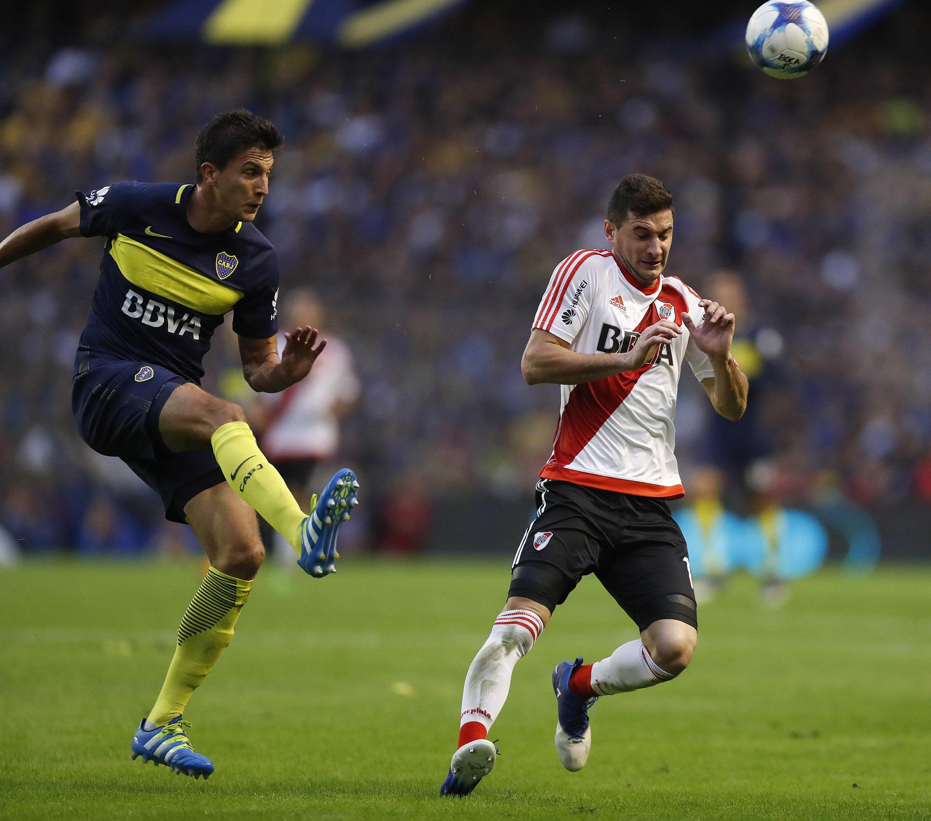 El jugador de Boca Santiago Vergini disputa el balón con Lucas Alario